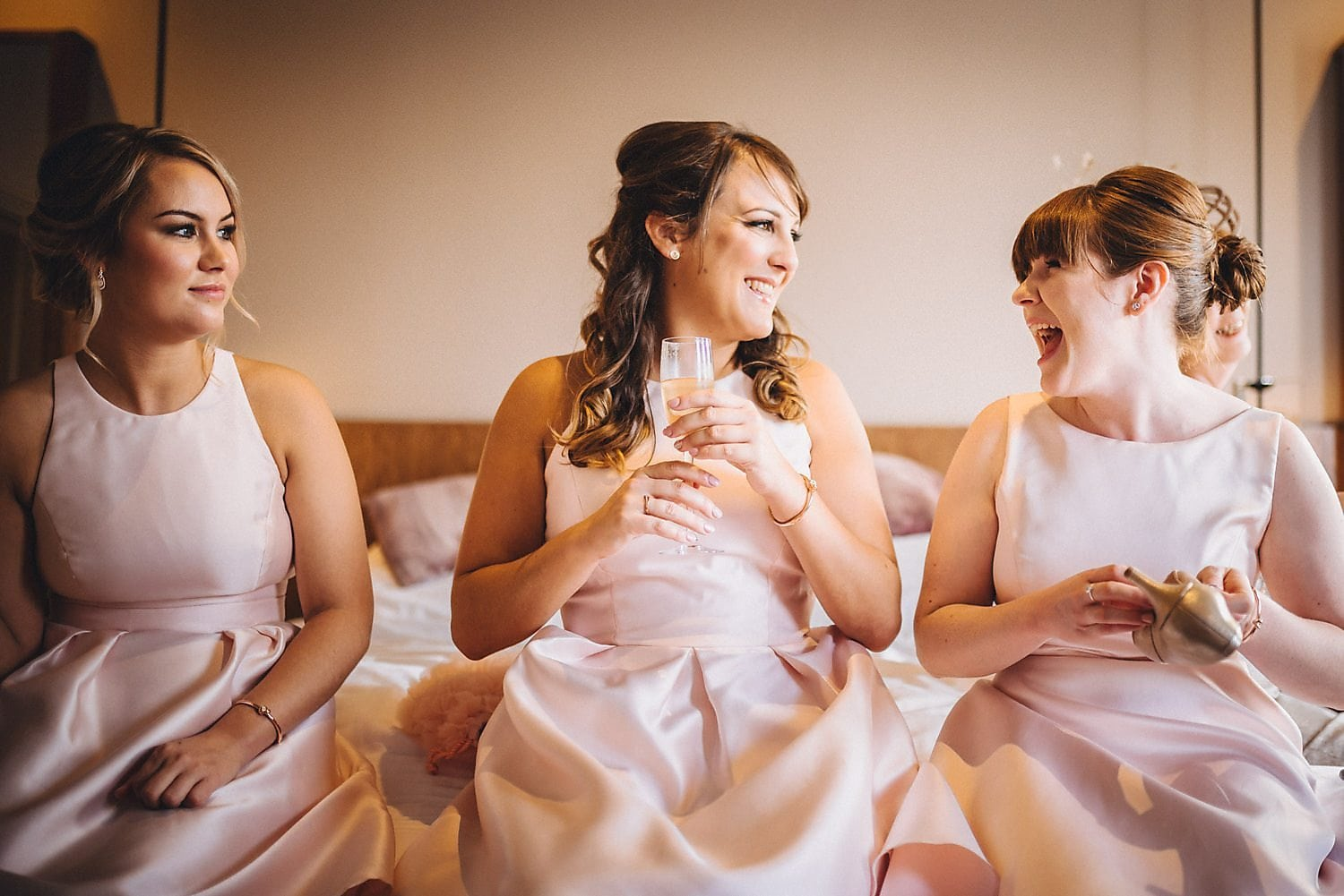 Bridesmaids laugh together in bridal suite