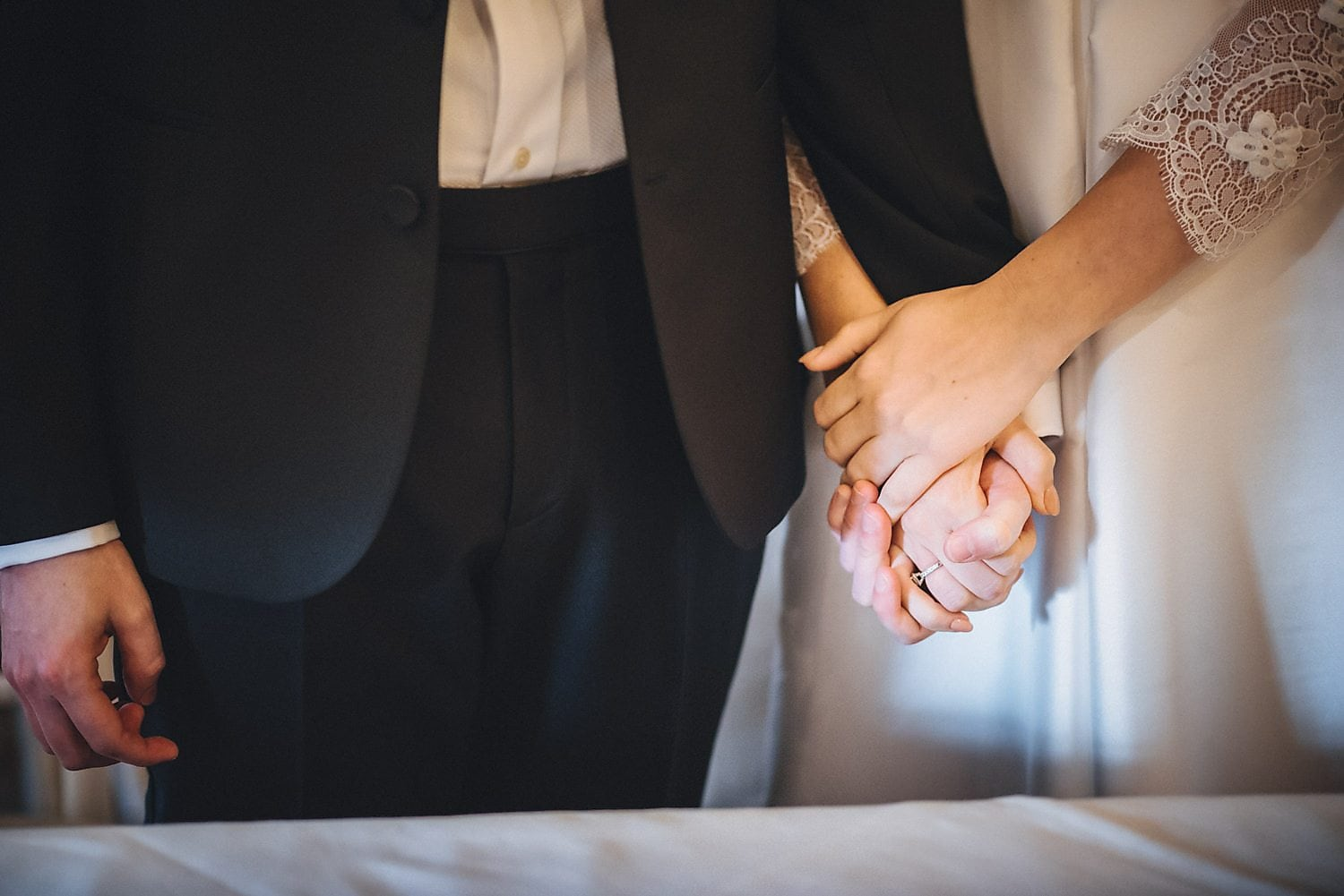 Close up shot of bride and groom holding hands