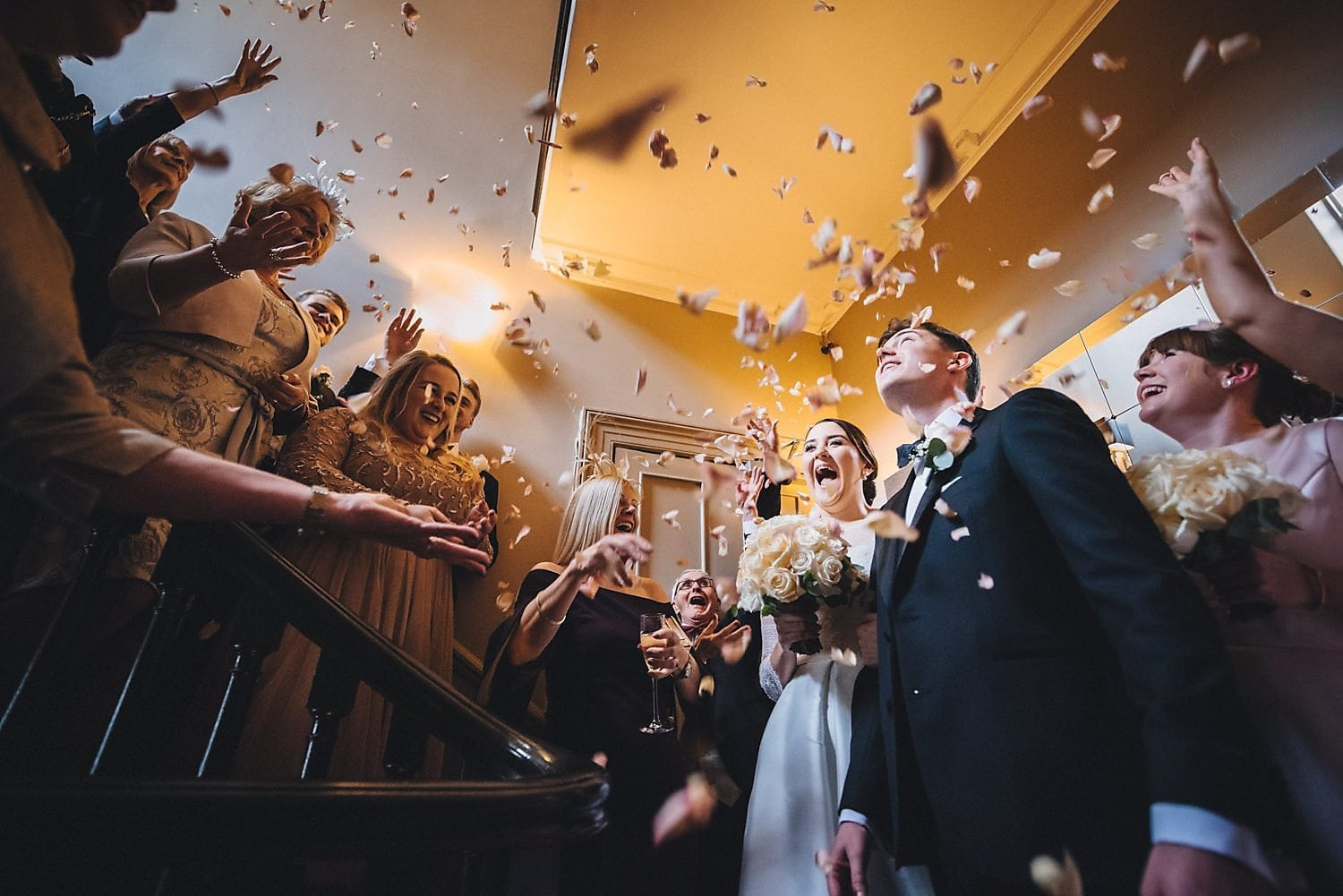 Rose petals thrown as confetti in stairwell at The Bingham