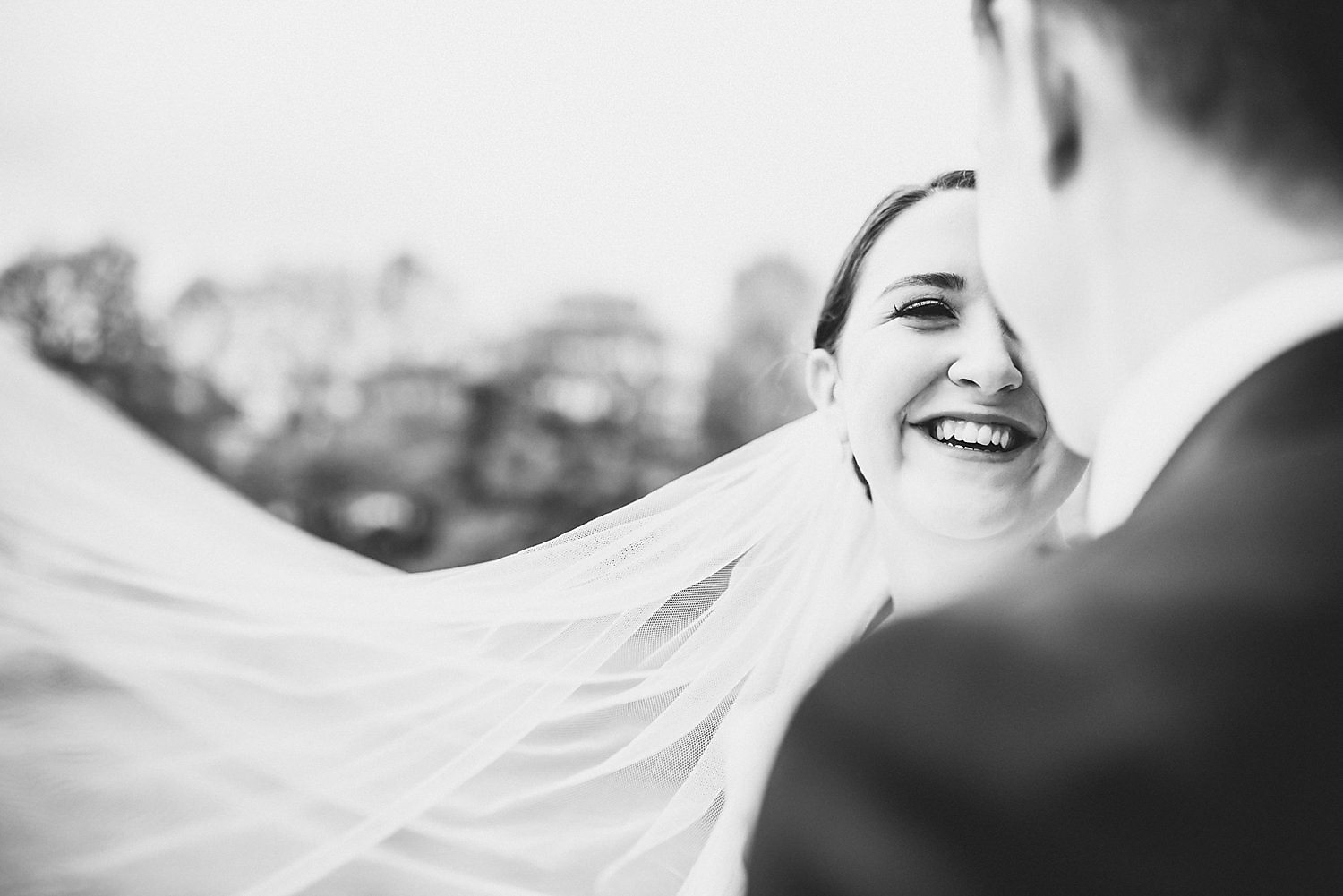 Black and white couple's portrait with bride's veil billowing to one side