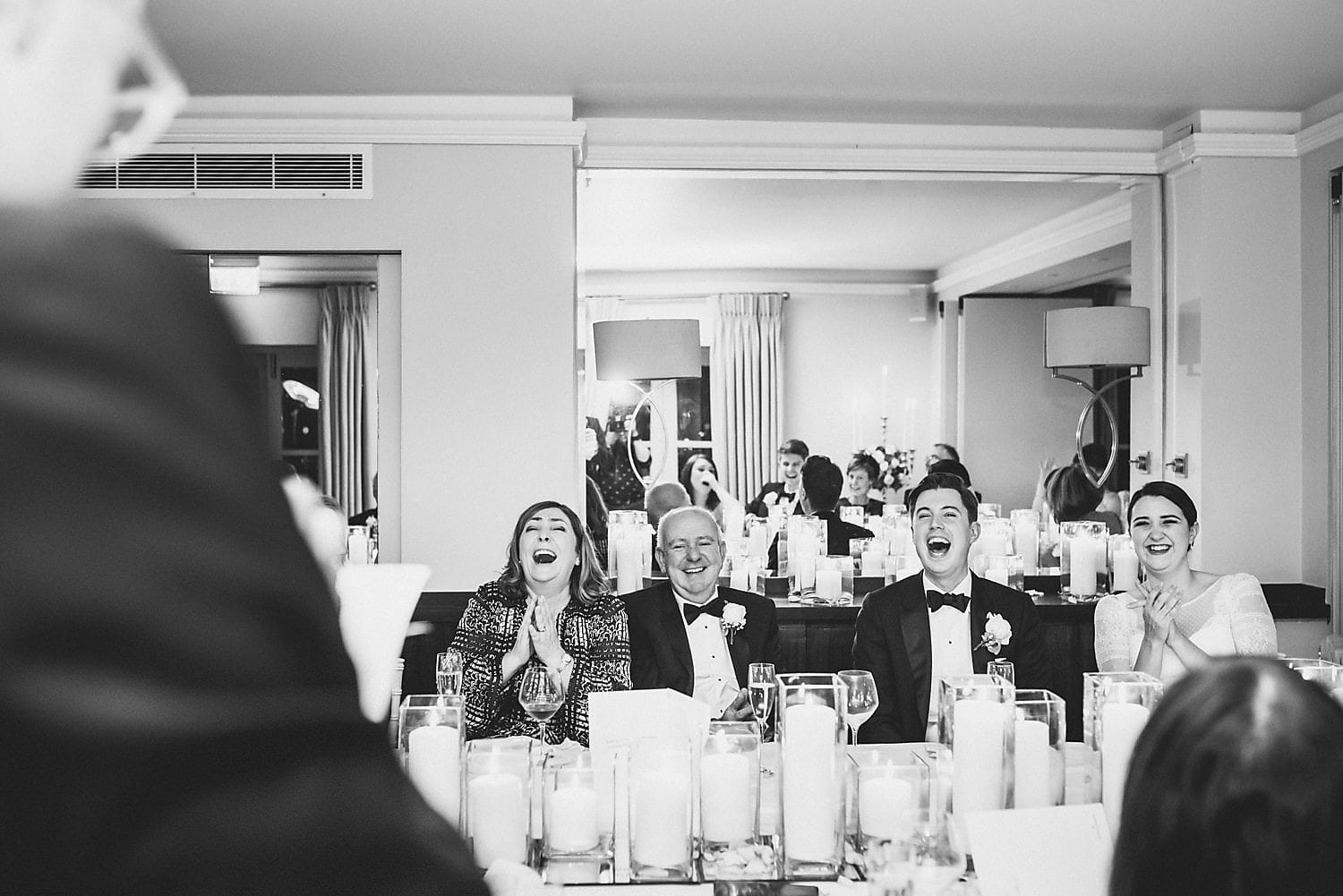 Black and white shot. Everyone laughing during best man's speech