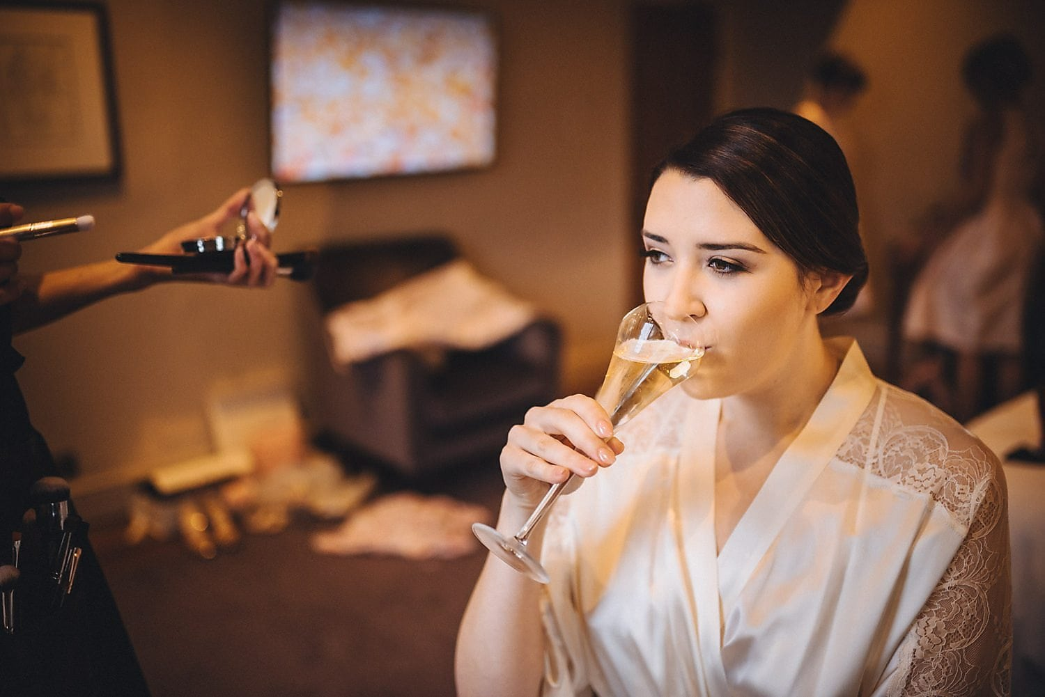 Bride sips champagne as she gets ready for her chic Bingham Hotel wedding