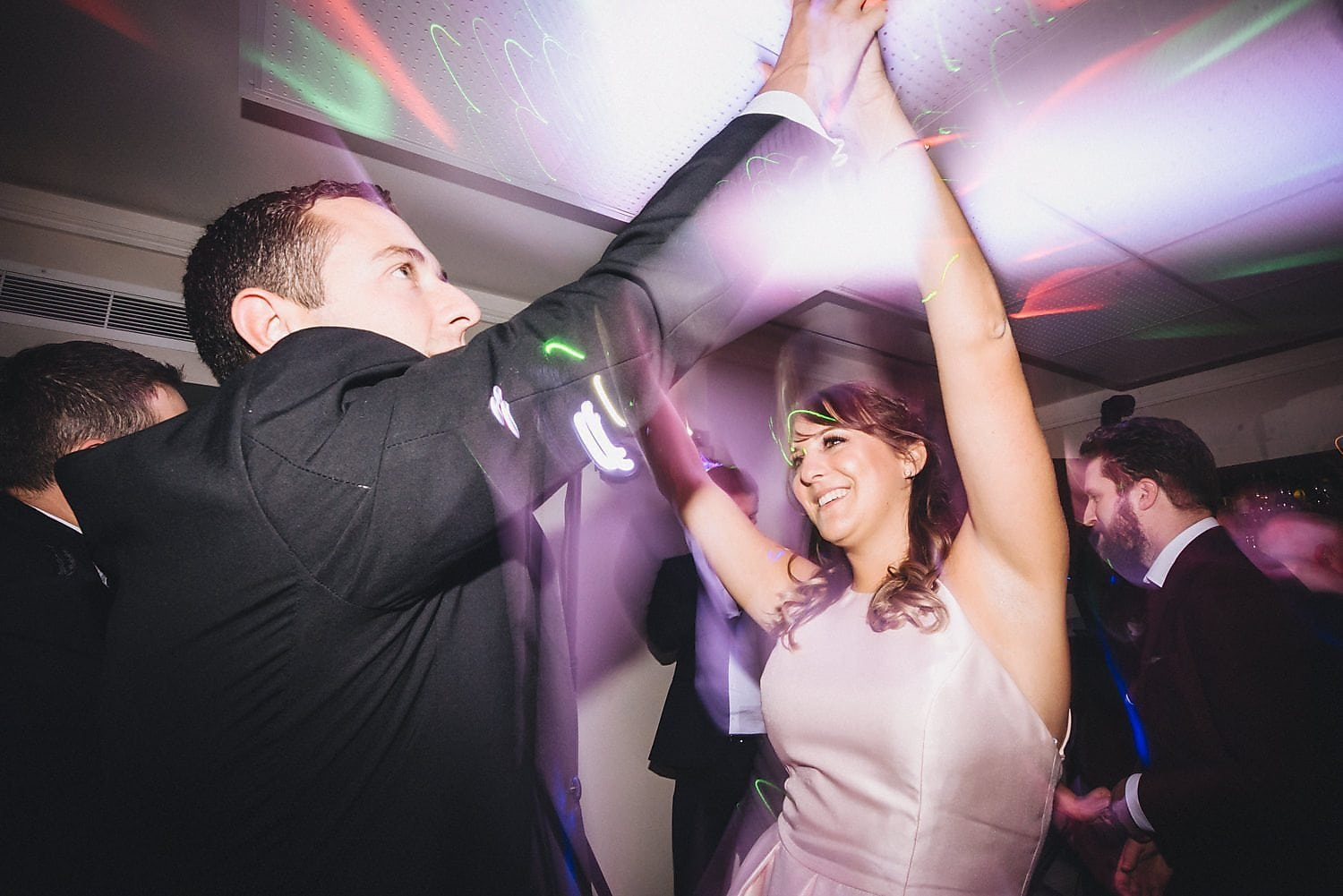 Bridesmaid dances with arms in the air