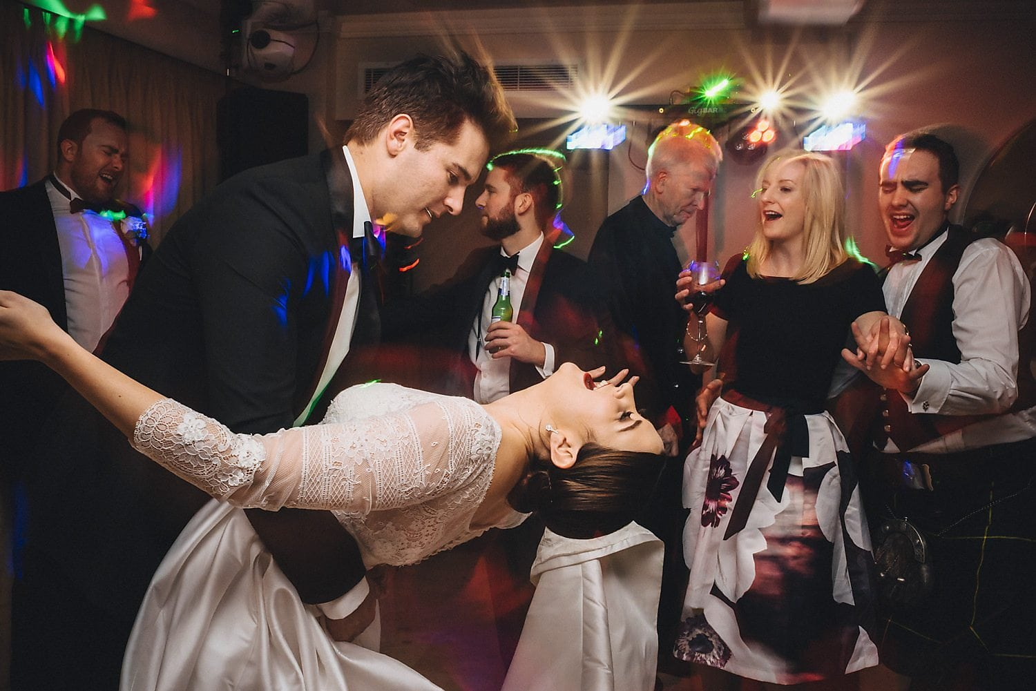 Groom dips bride low on the dancefloor