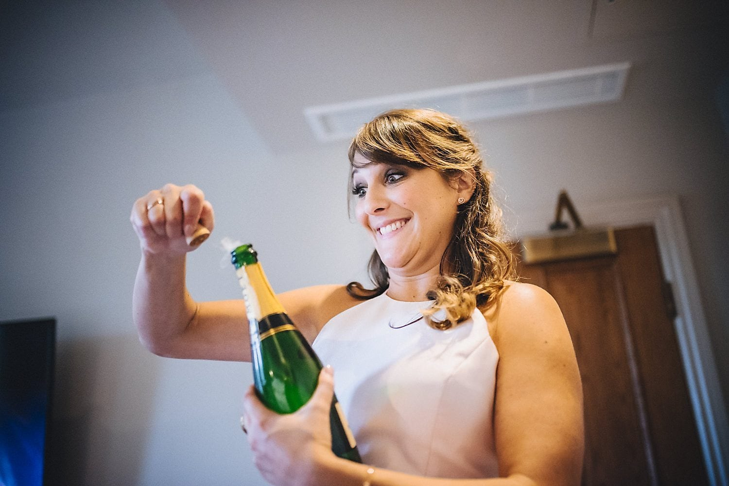 Bridesmaid pops bottle of champagne