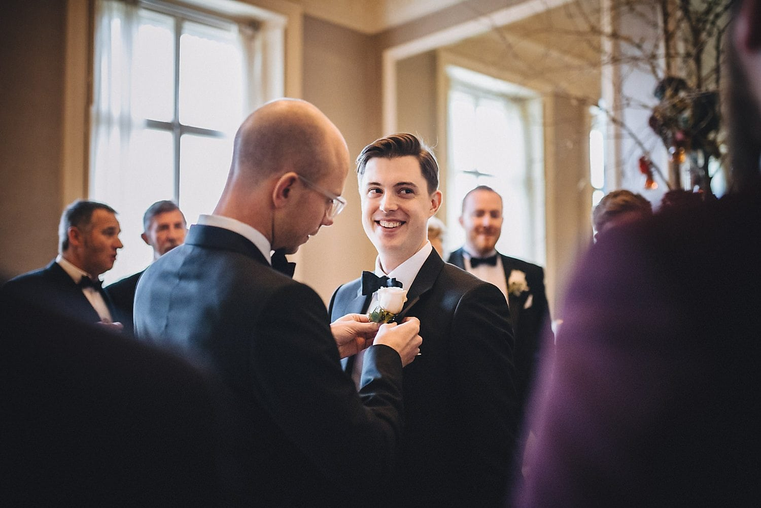 Best man fixes groom's buttonhole for his Chic Bingham hotel wedding