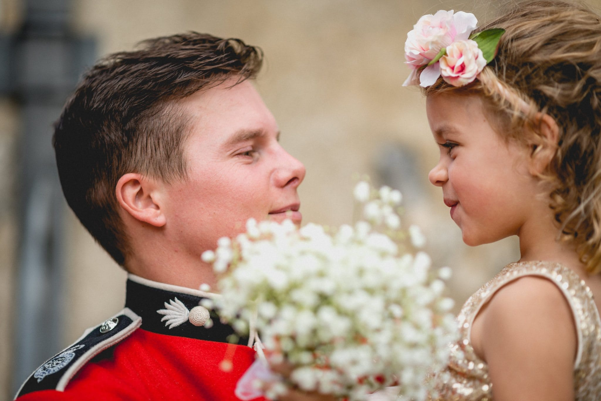 Groom gives cute flower girl a hug