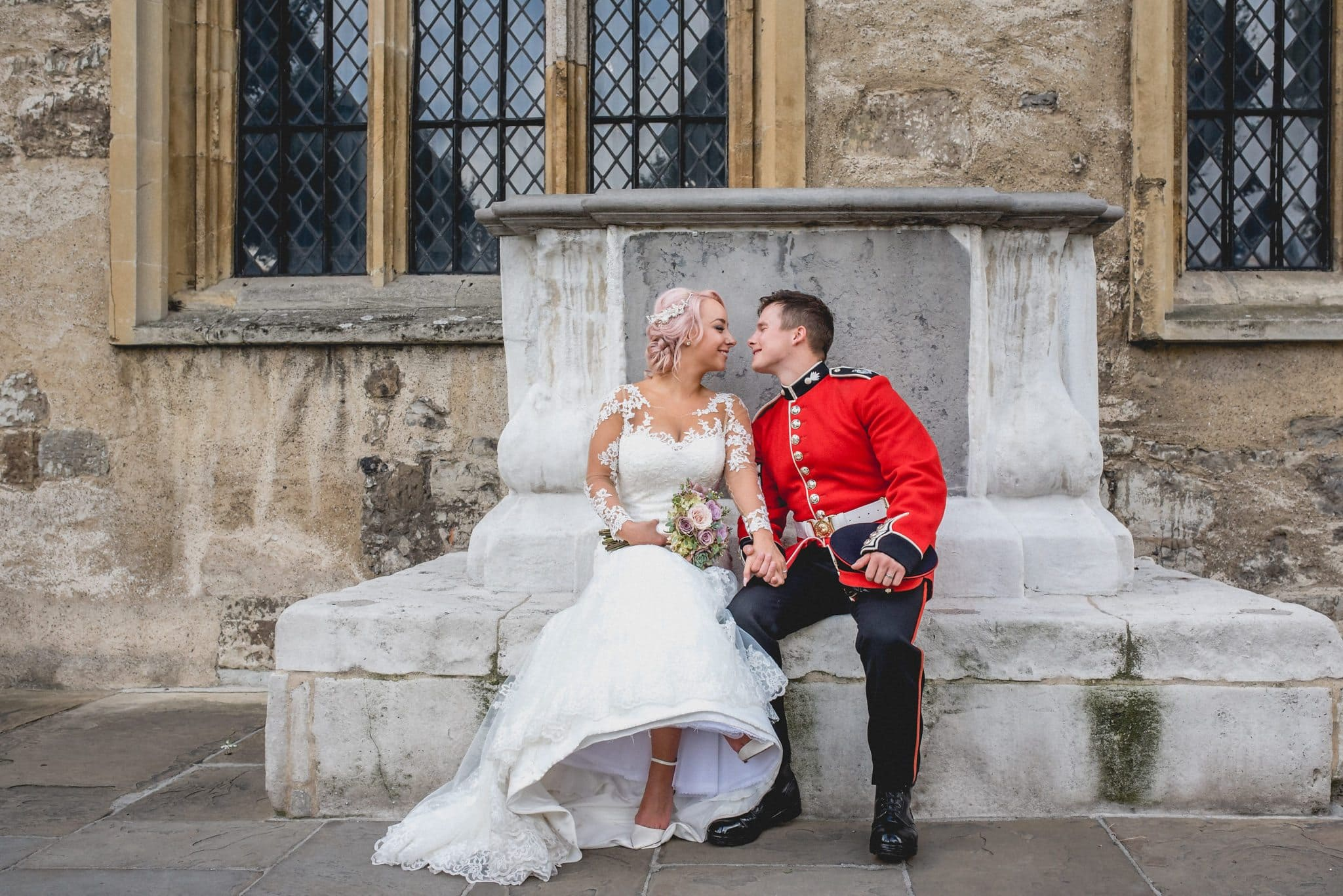 Couple shot of bride and groom outside Tower of London. Groom wears Royal Guard red dress uniform, bride has pale pink hair and wears a dress with illusion lace sleeves.