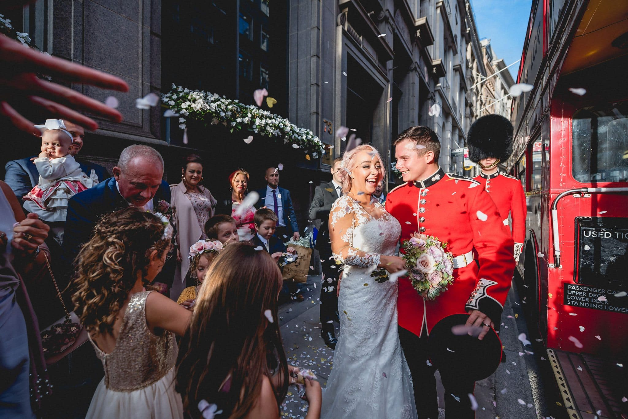 The newlyweds arrive at their reception venue by London bus amid a shower of confetti