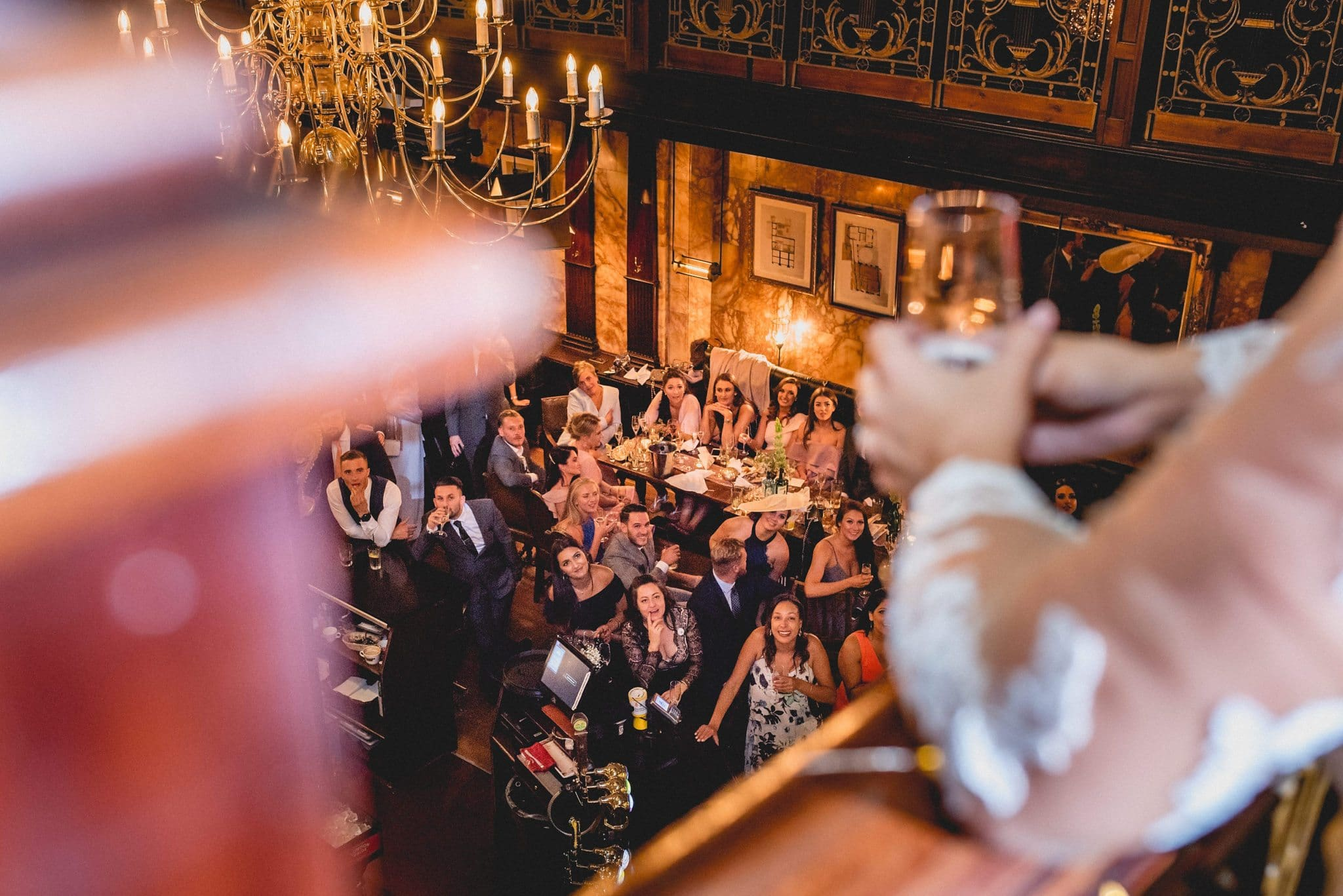 Shot from the balcony of The Counting House pub - guests look up smiling as the bride and groom give speeches