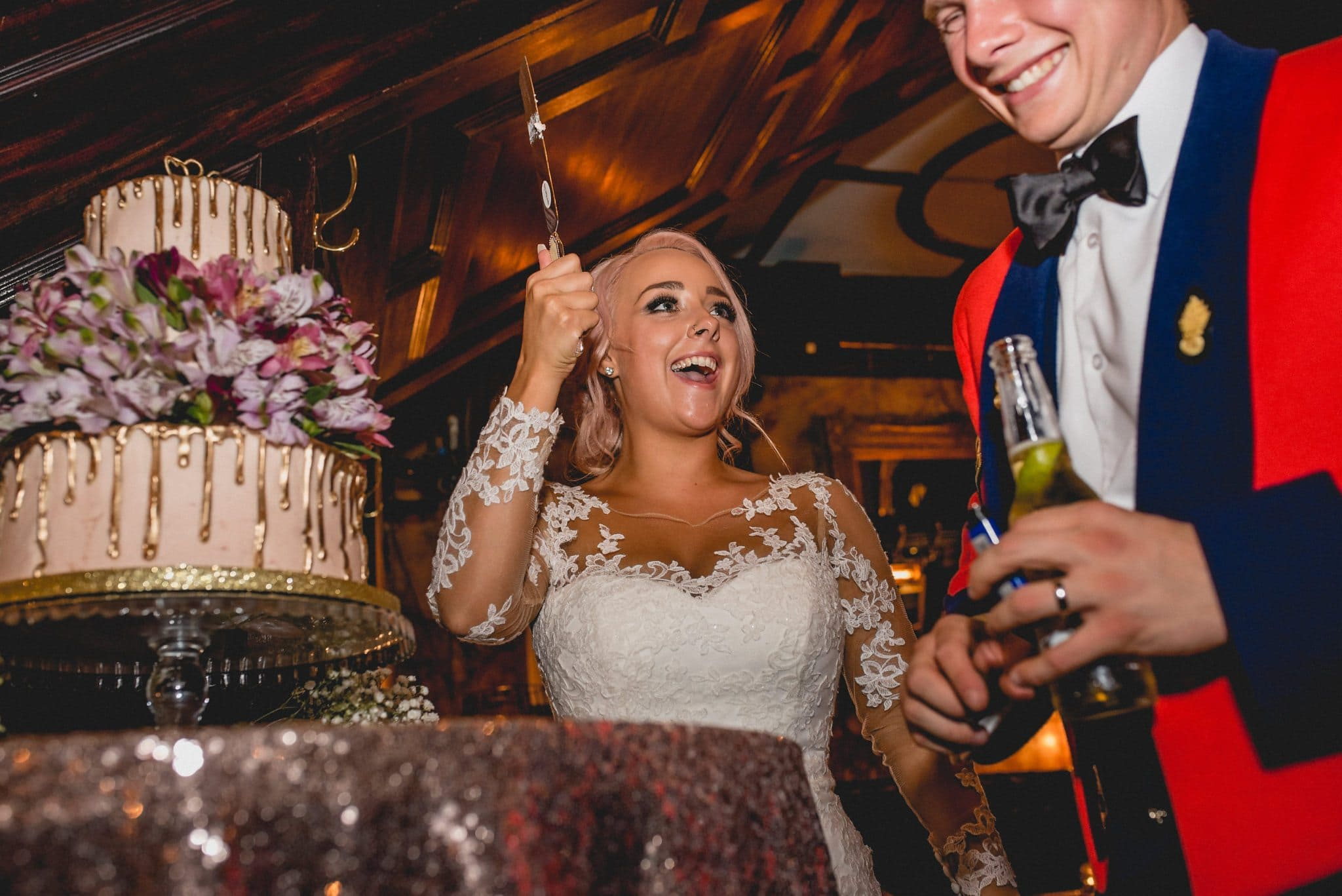 Bride brandishes knife and giggles as she prepares to cut the cake. Cake is adorned with flowers and a gold drip.