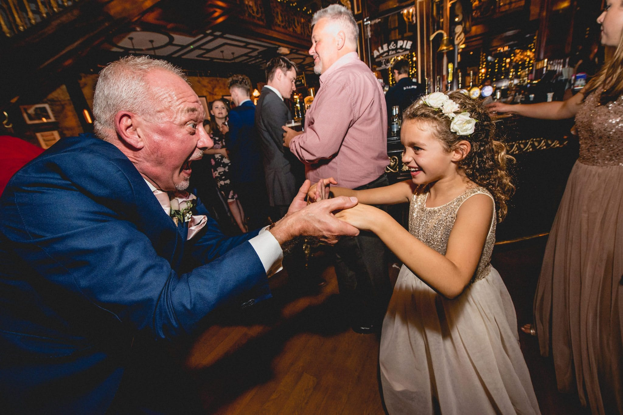 Flower girl dances with a guest at the reception