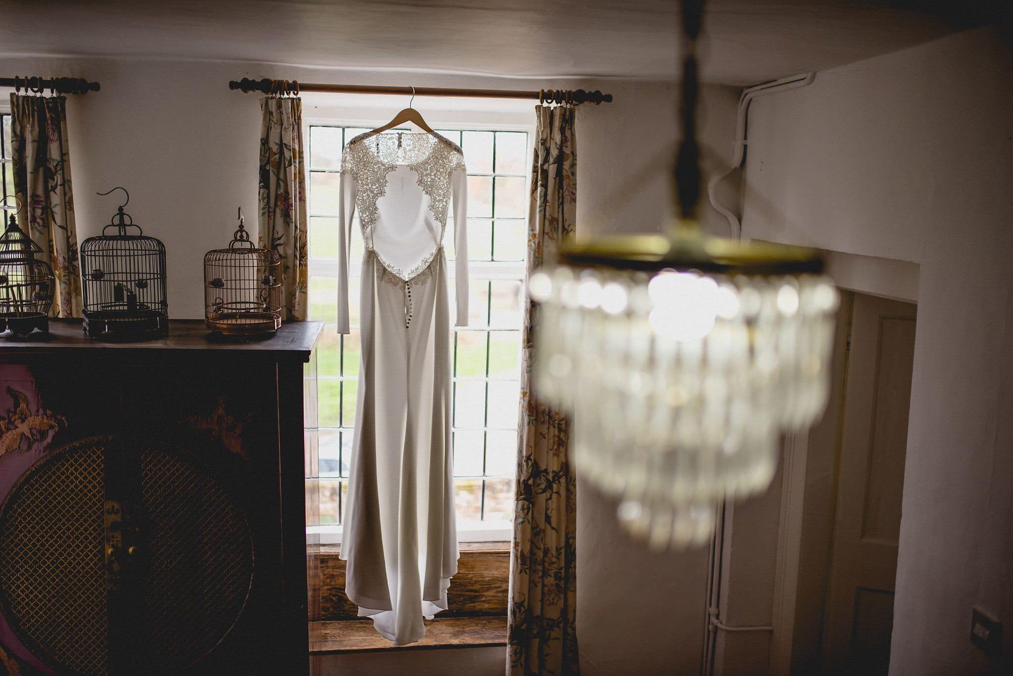 Bride's dress hangs in the window at Littlefield Manor