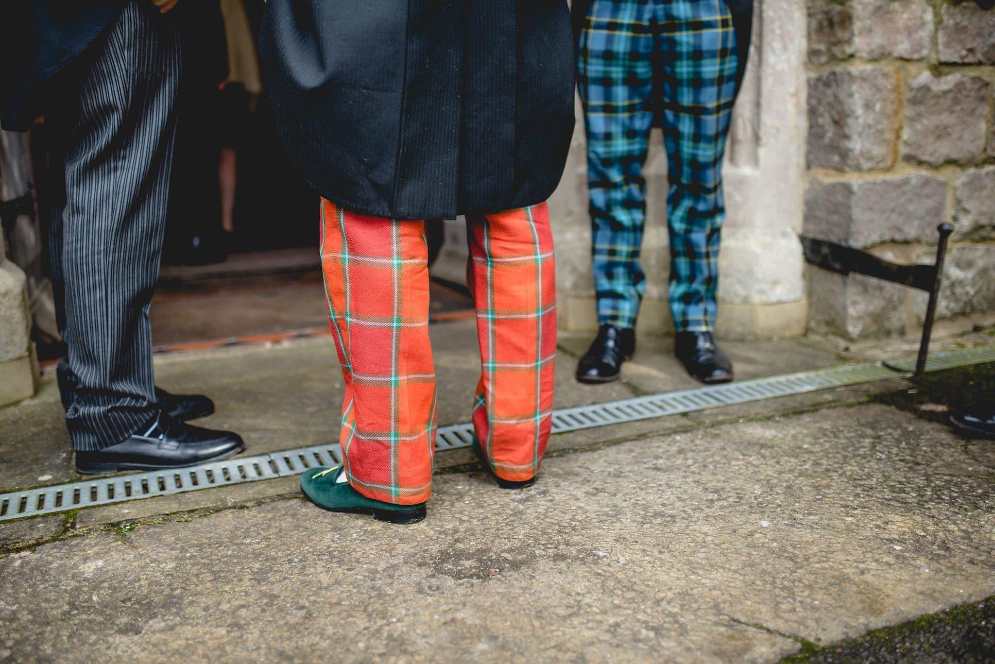 Groom wearing tartan trousers in the church doorway