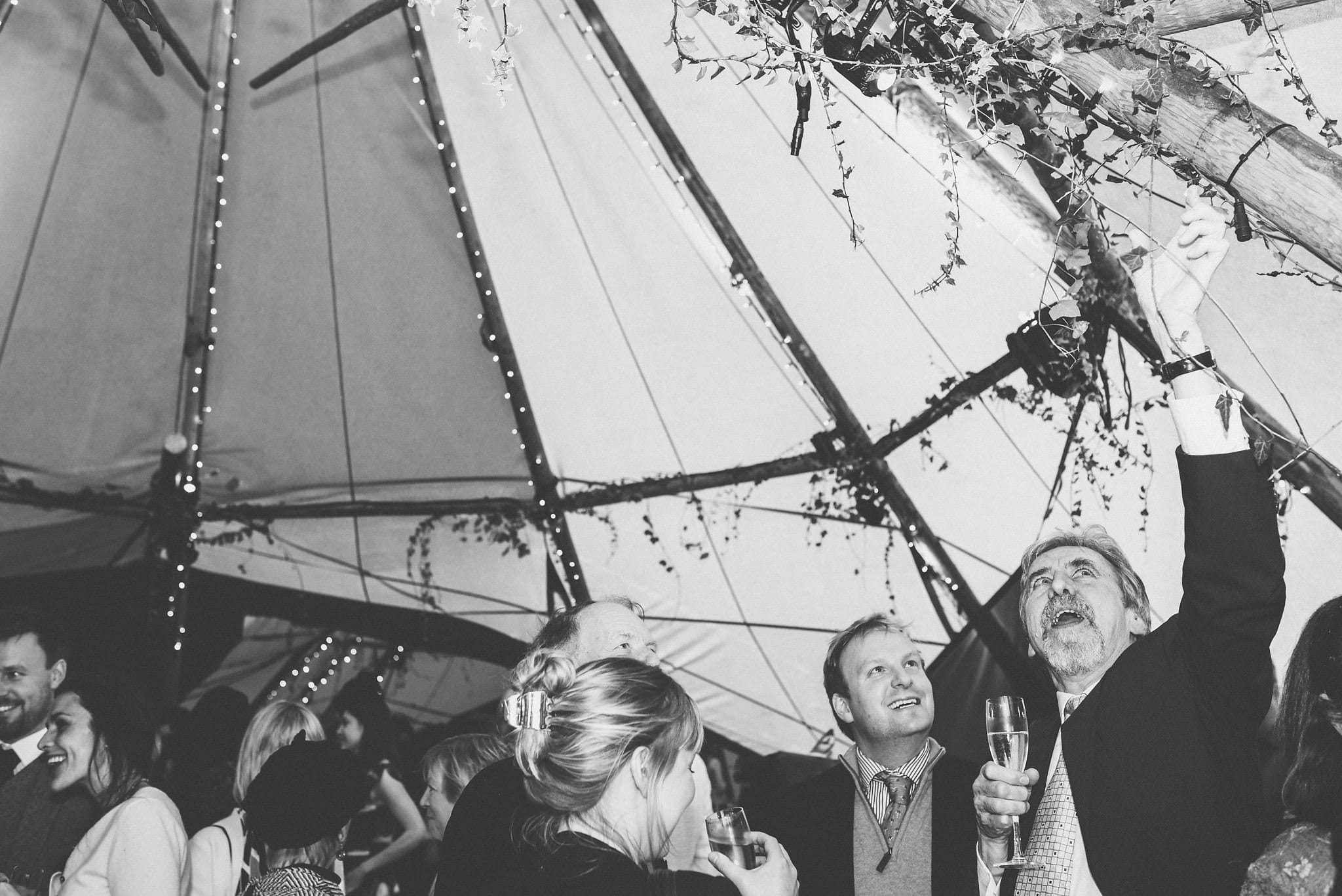 Black and white candid shot of guests mingling in tipi.