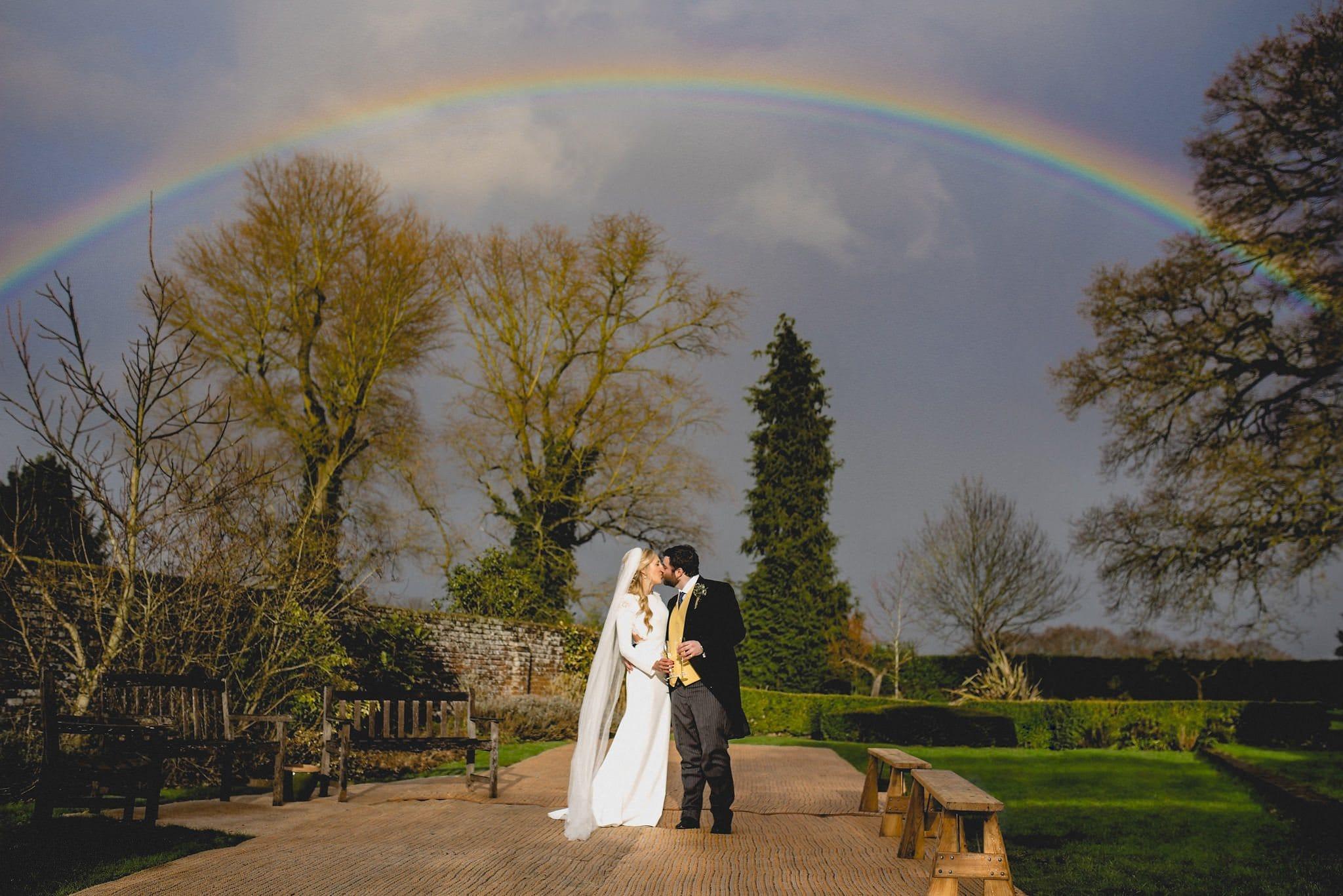 Bride and groom kiss with a rainbow overhead