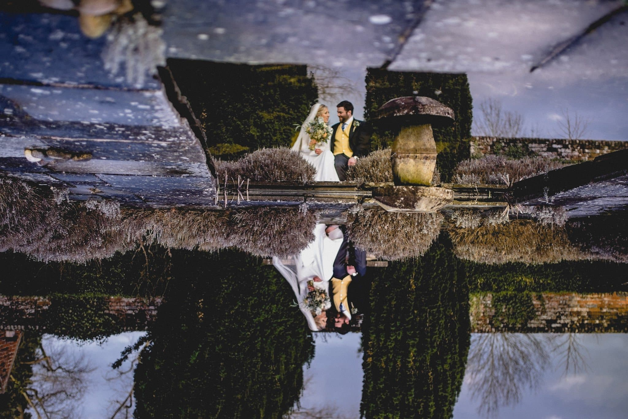 Couple's portrait and reflection in a pond at Littlefield Manor