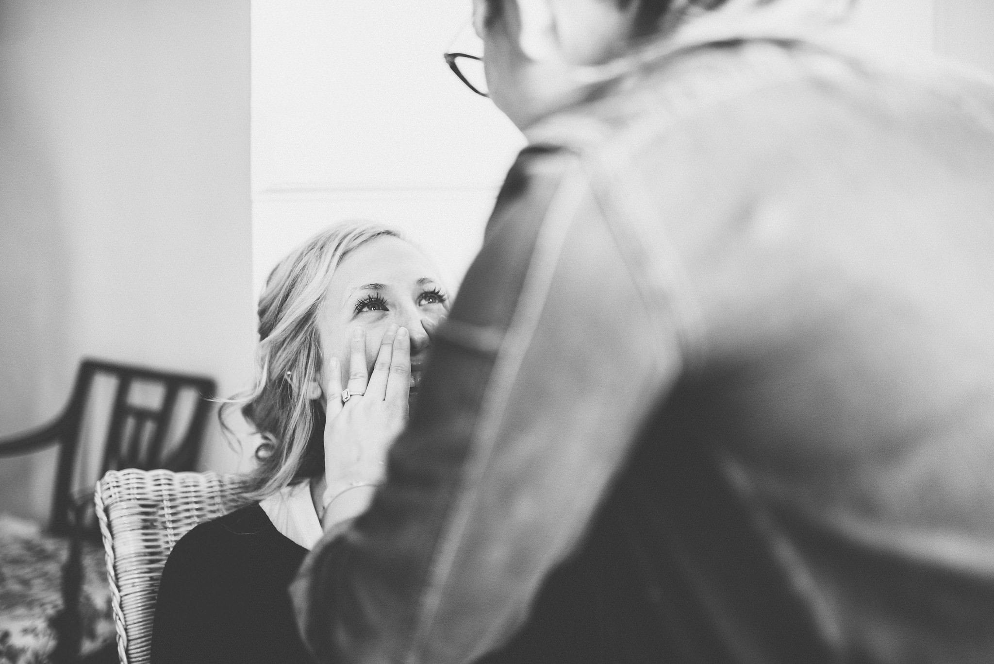 Black and white shot of bride getting ready on the morning of her stylish tipi wedding