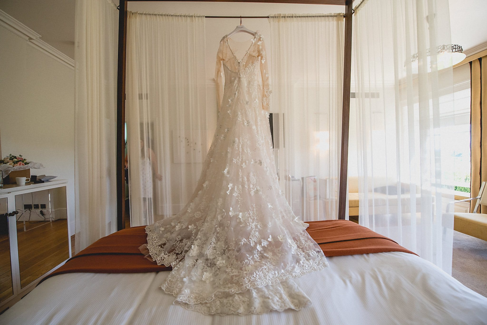 Bride's dress hangs above the bed at The Grove hotel