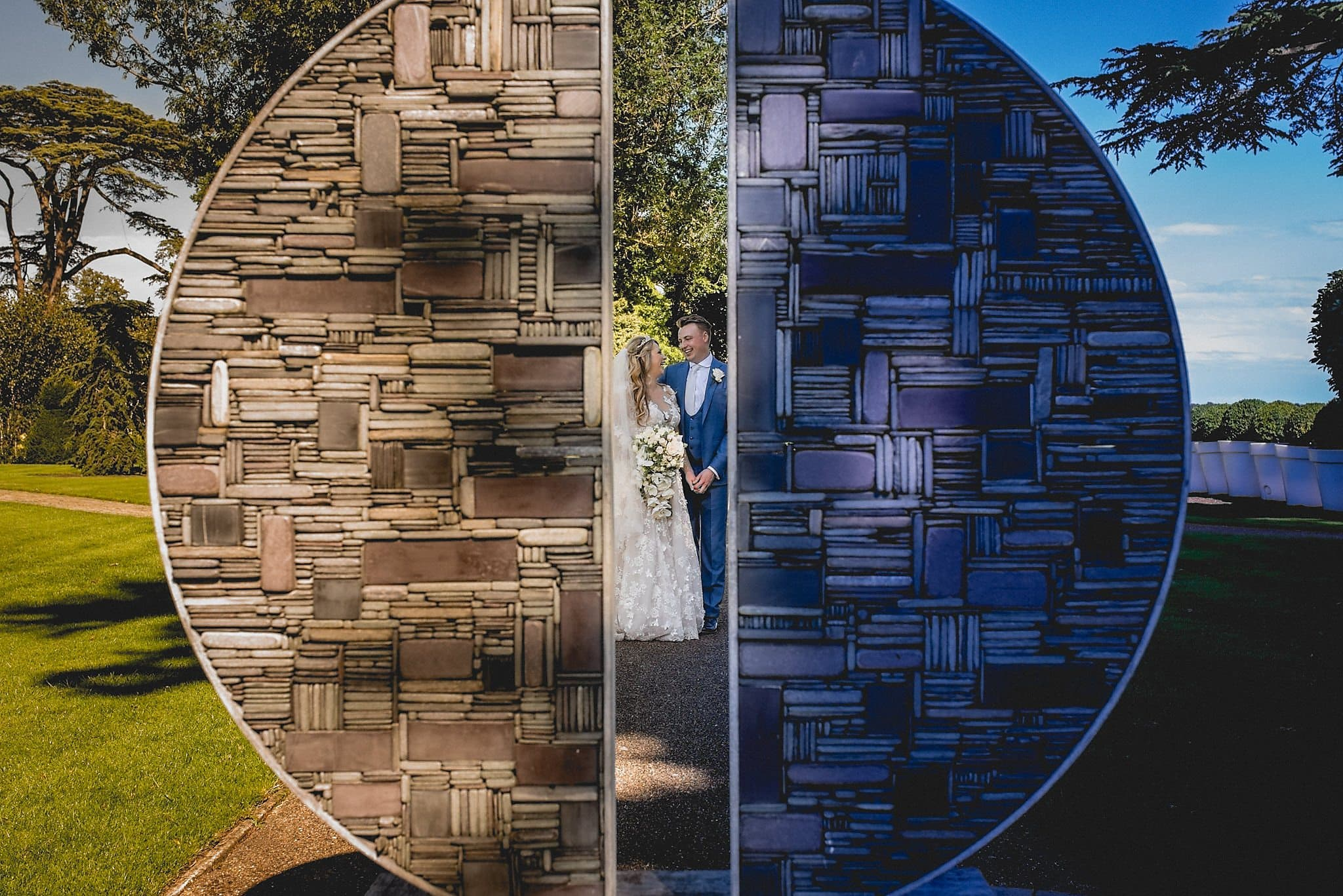 Bride and groom shot through the opening of a circular piece of modern art in the grounds of The Grove hotel