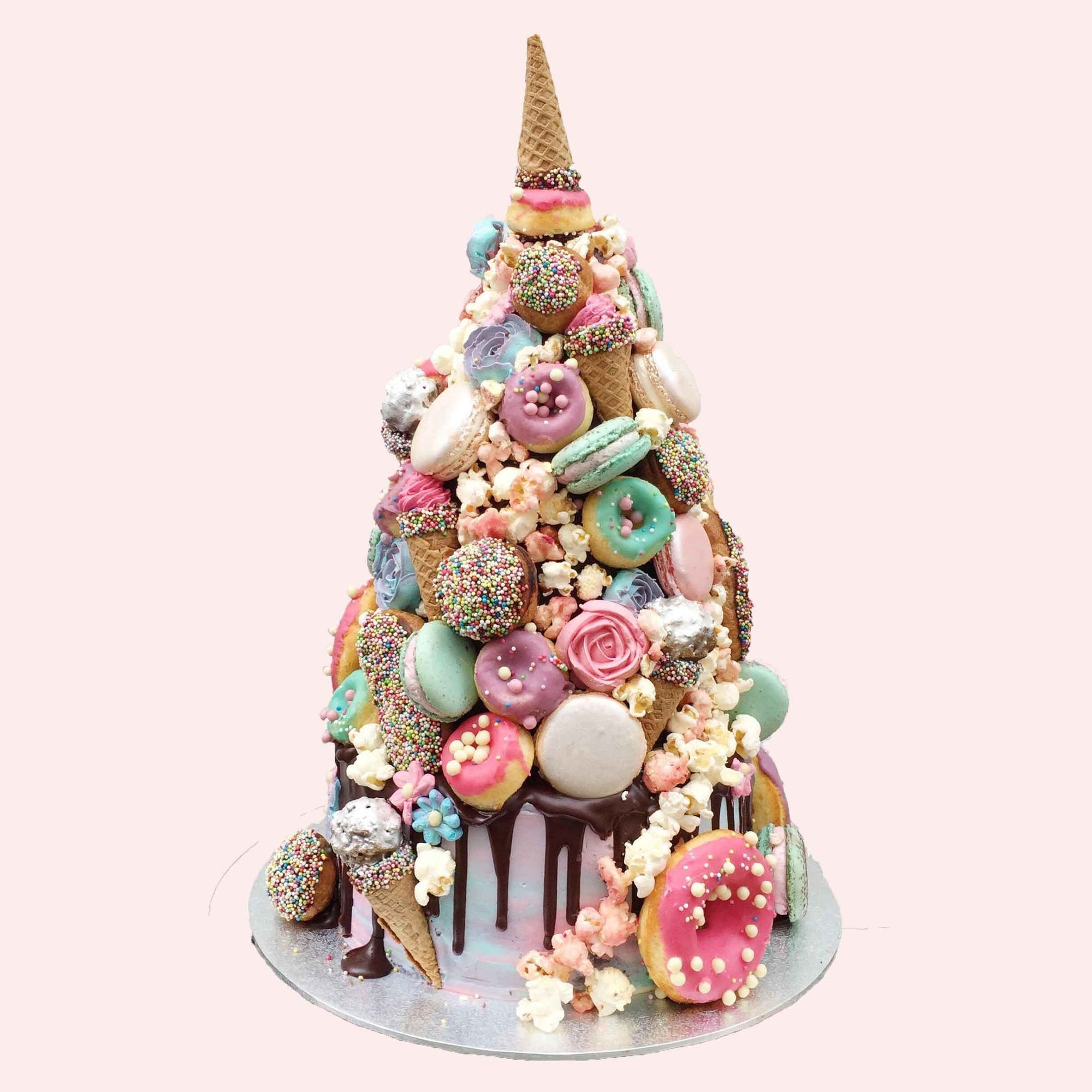 Anges de Sucre's take on a croquembouche. Cake tower piled with donuts, piped flowers, macarons, popcorn with a cornet 'unicorn horn' on top.