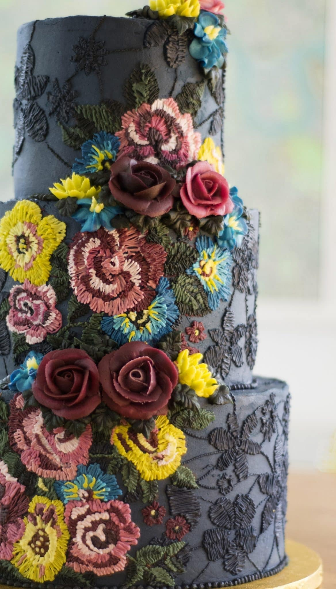 Three tiered buttercream cake from Emma Page with embroidery style texture and piped buttercream roses