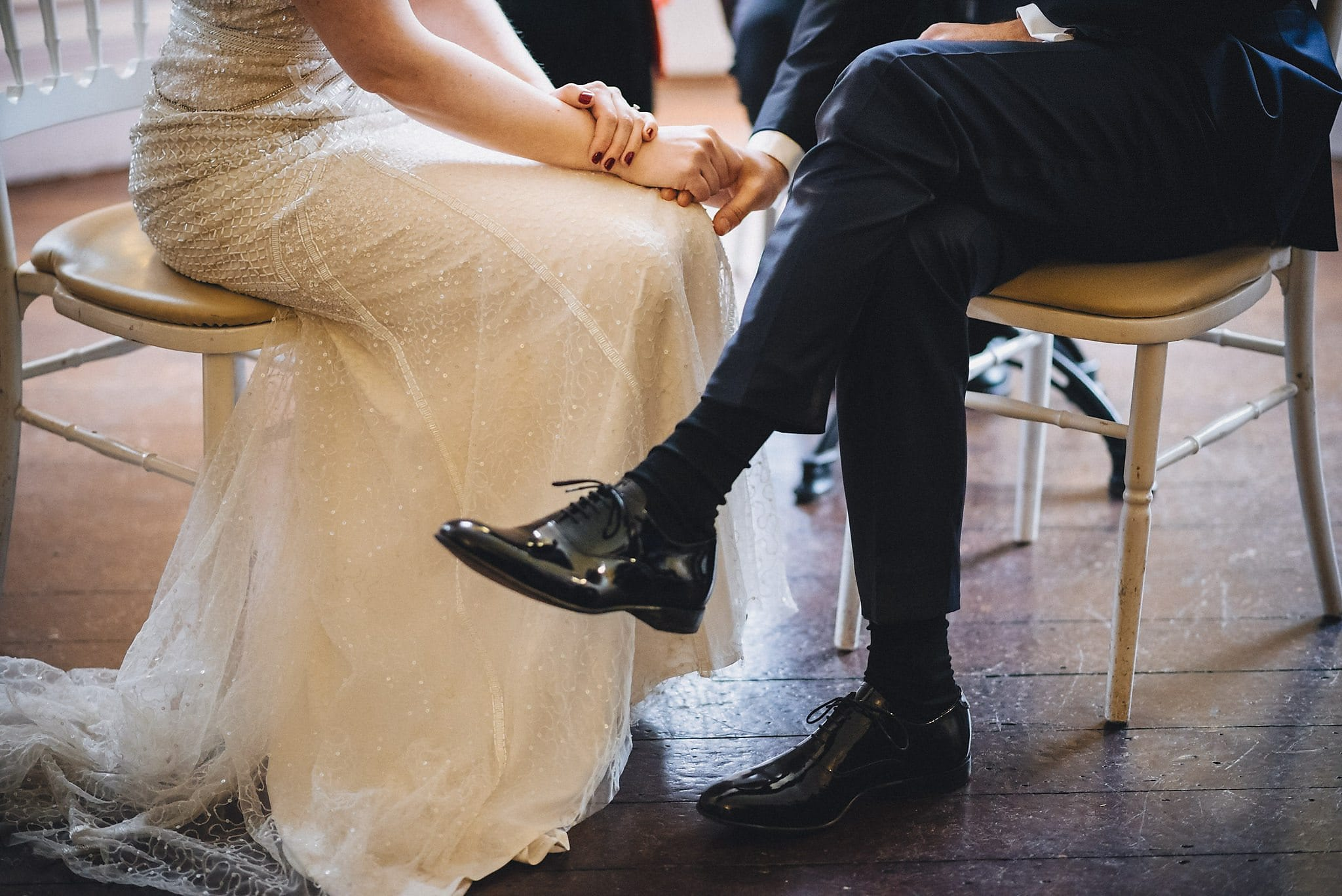 Shot of bride and groom's legs and shoes while seated at wedding ceremony