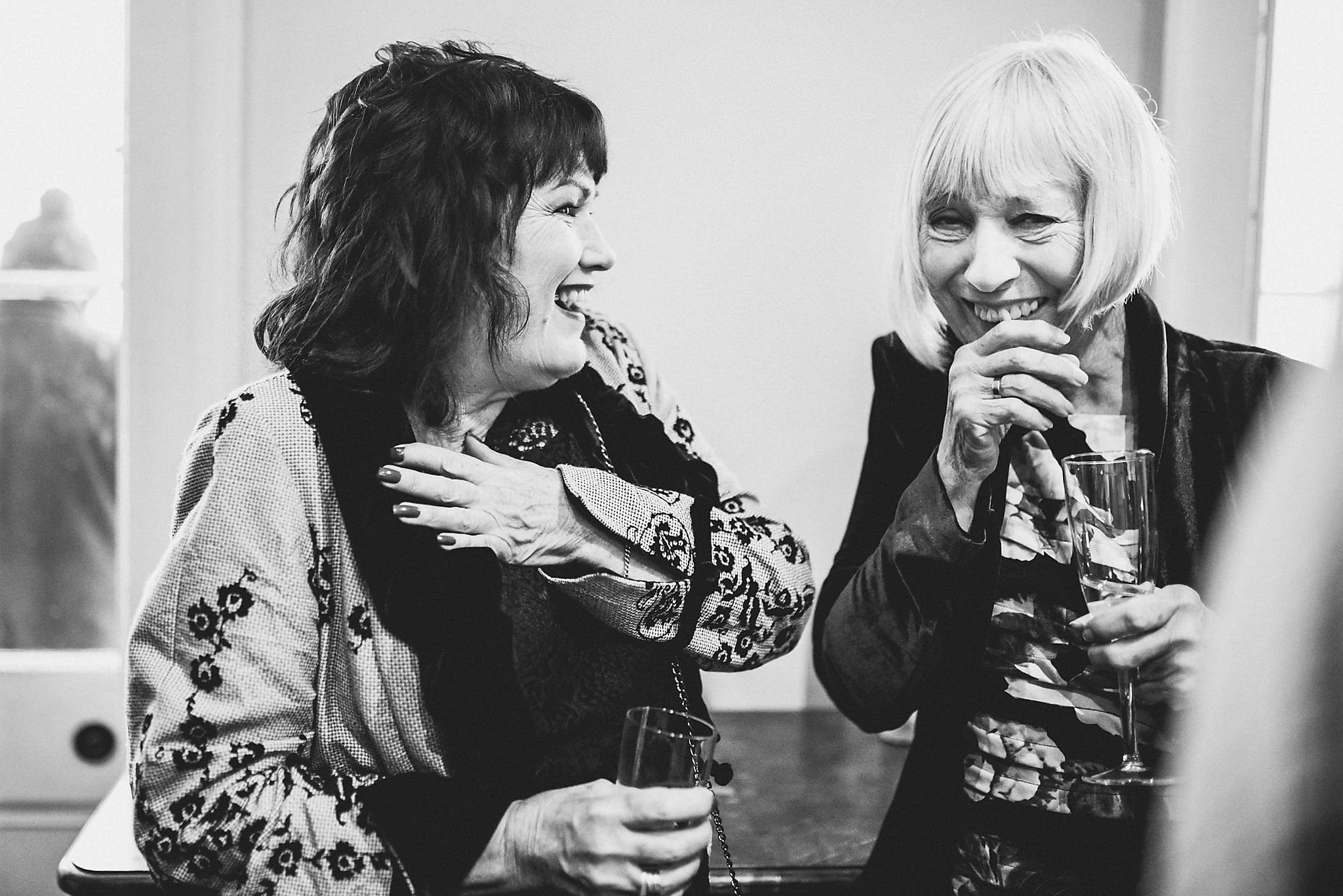 Bride and Groom's mums laughing together at their Clissold House wedding