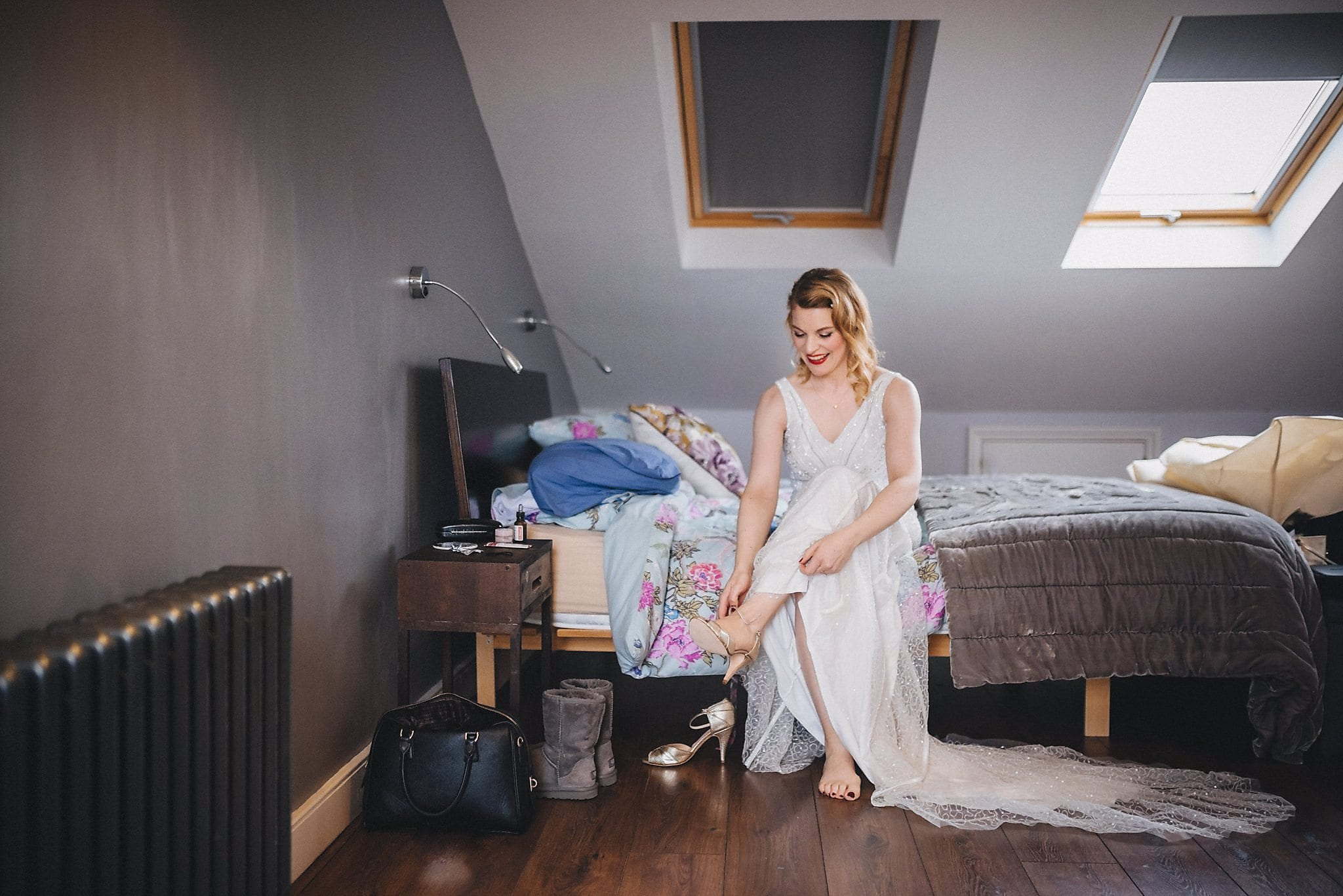 Bride sits on bed and puts her shoes on