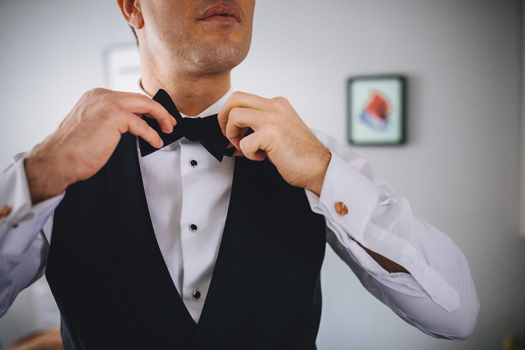 Groom fastening bow tie
