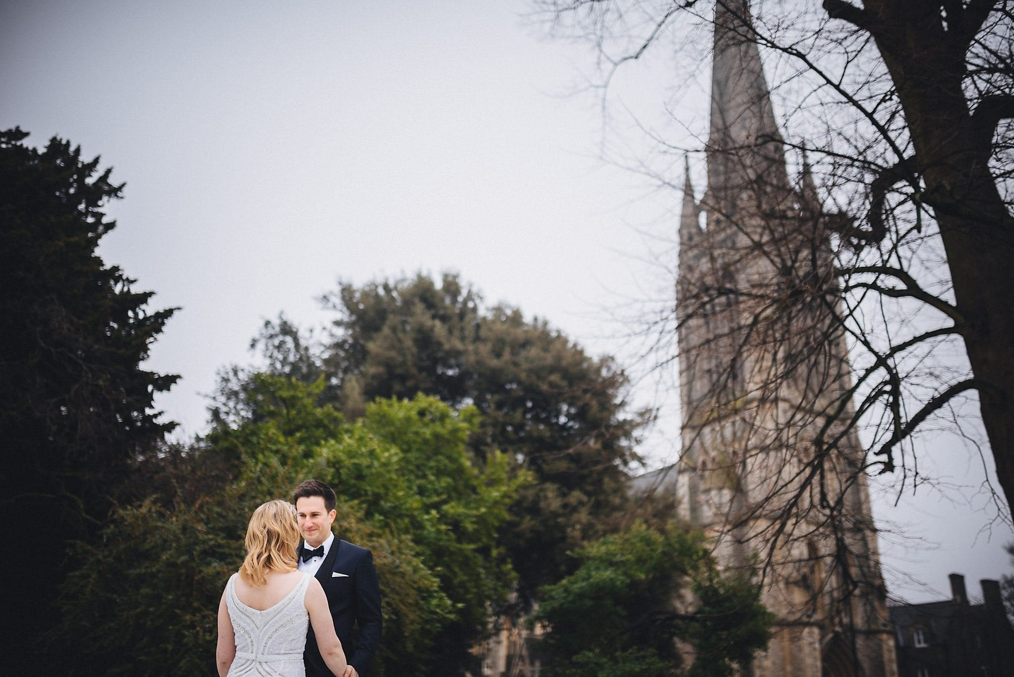 Bride and groom in Clissold Park with church in background