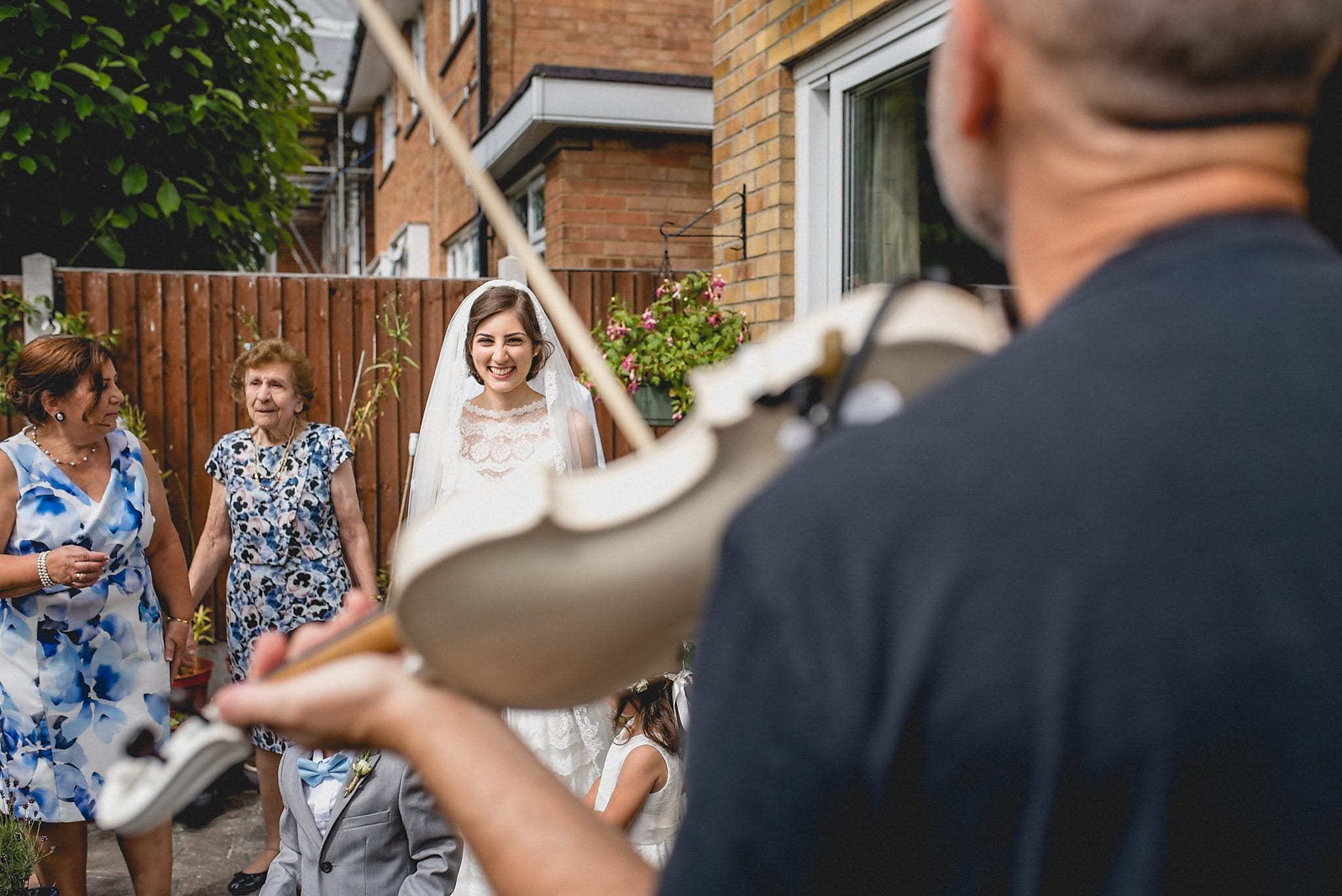 Fiddler plays white violin as bride prepares for her modern Greek wedding in her garden