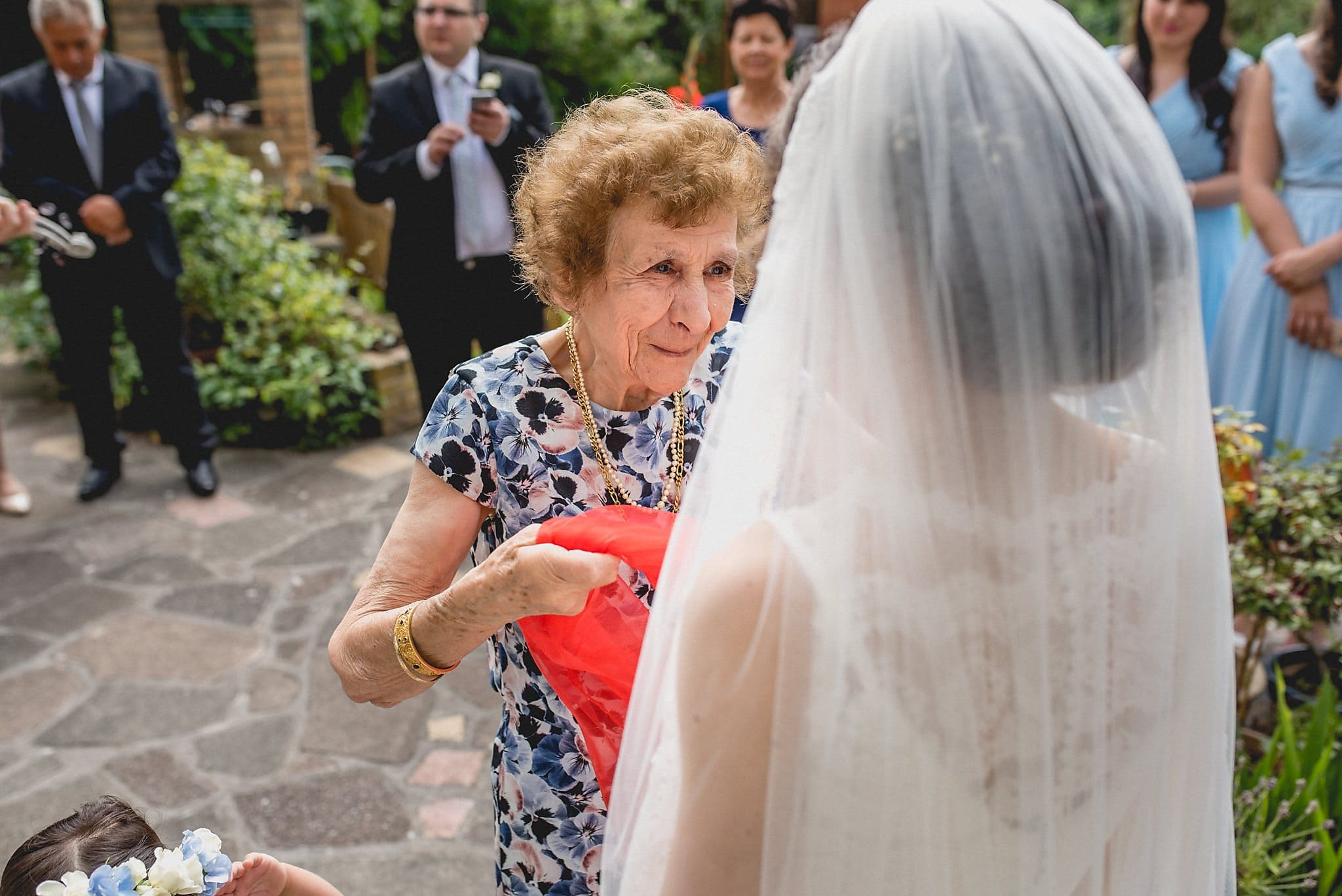 Grandmother wrapping red scarf around the bride in a Greek Wedding blessing