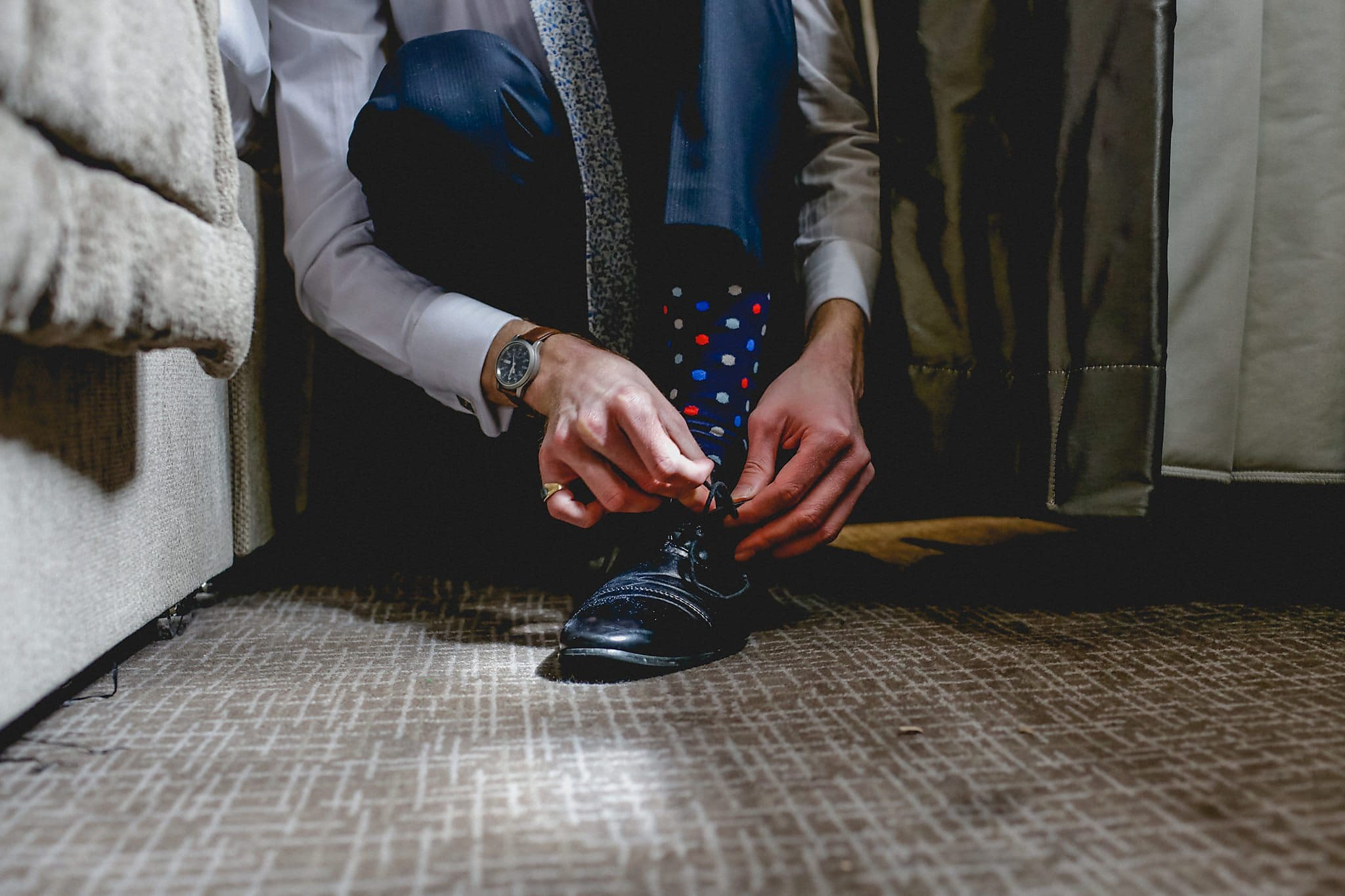Groom ties his shoe, wears polka dot socks