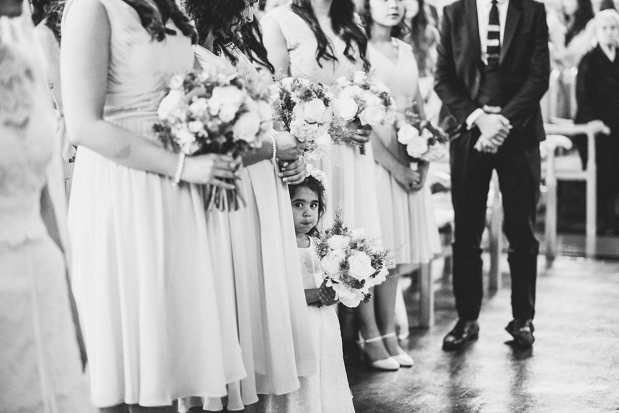 Black and white shot of bridesmaids with flower girl peeking out