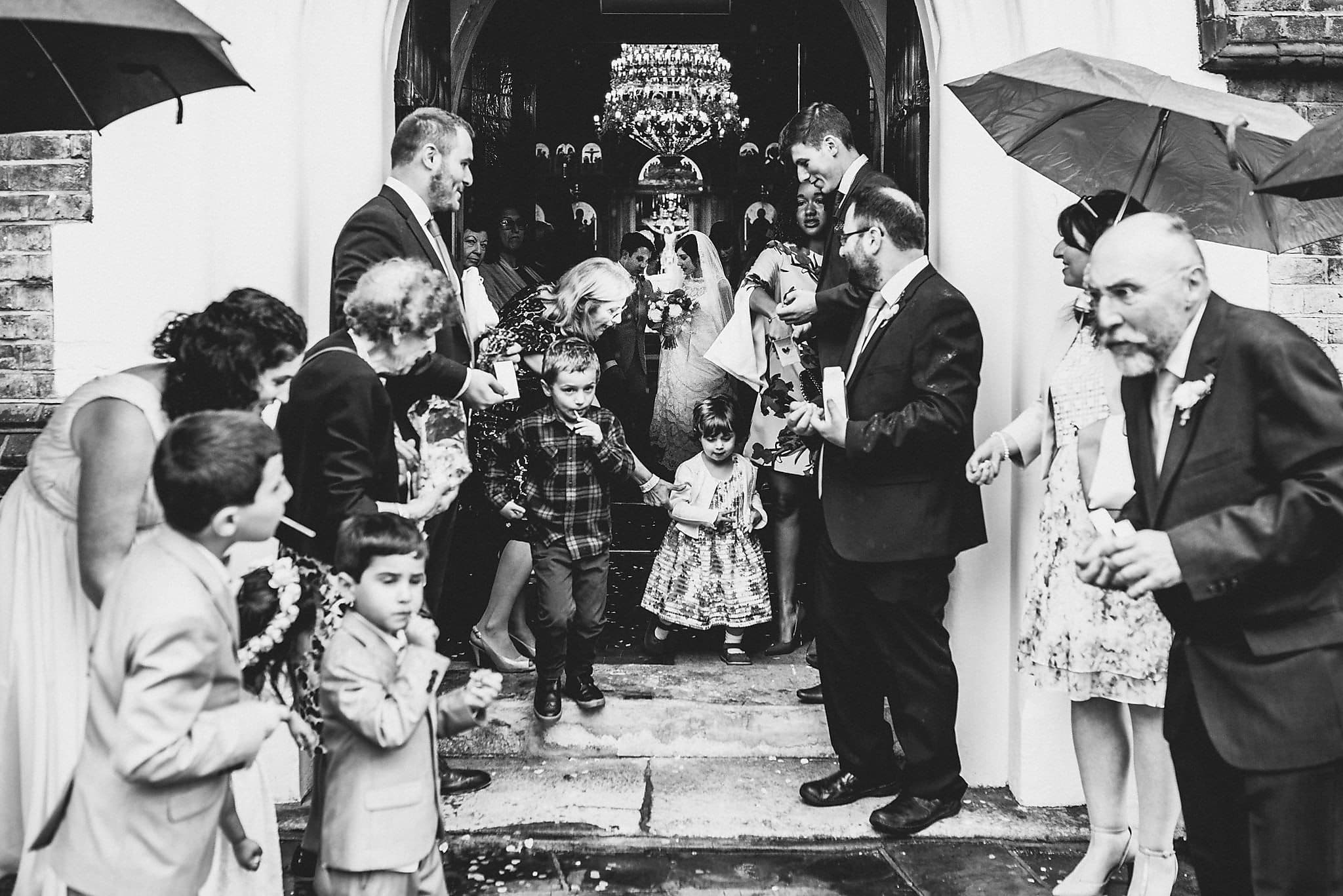 Wedding guests getting ready to throw confetti in the rain at Saint Andrew's Greek Orthodox Church