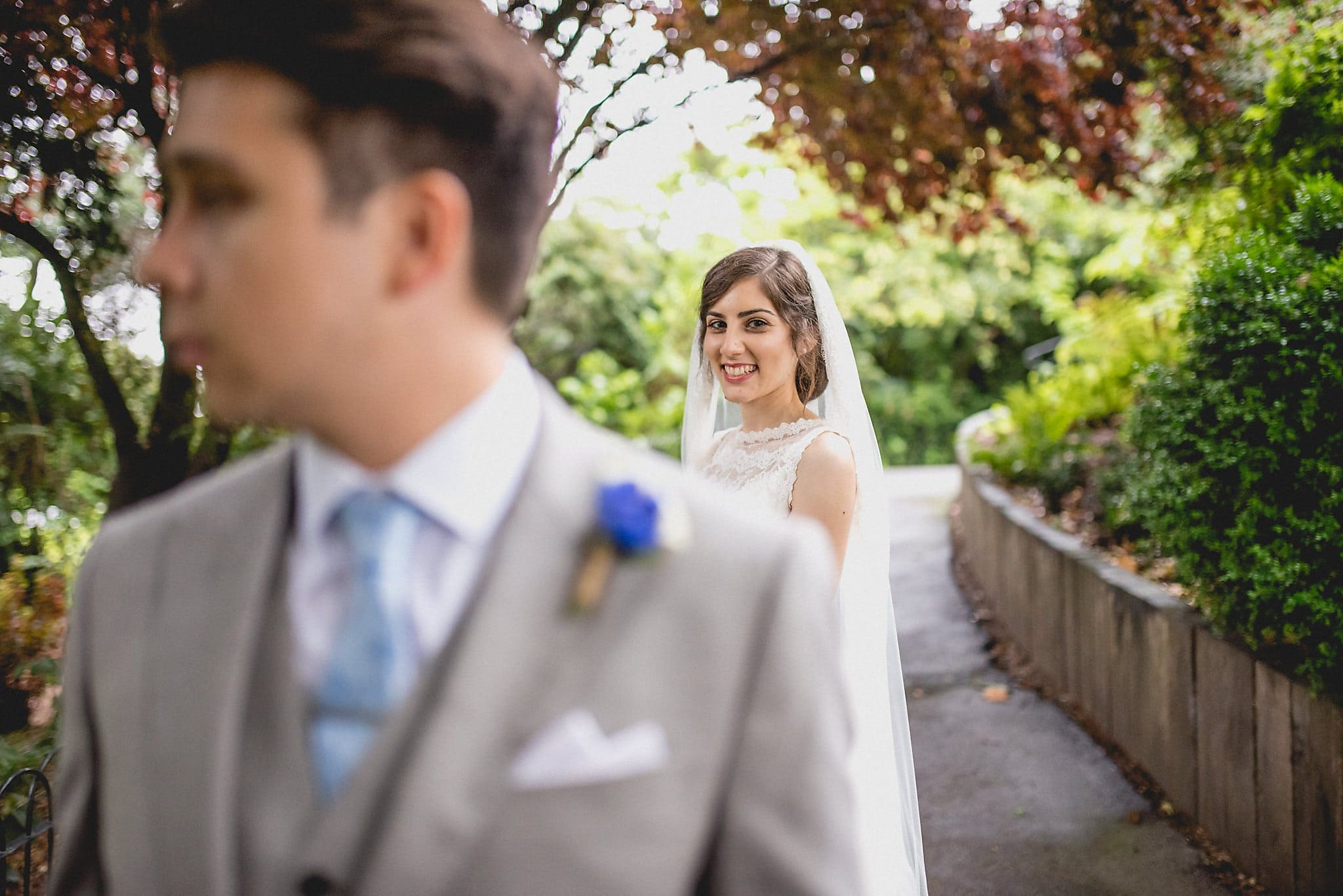 Bride in focus, groom in foreground out of focus during couple's shoot in Regent's Park