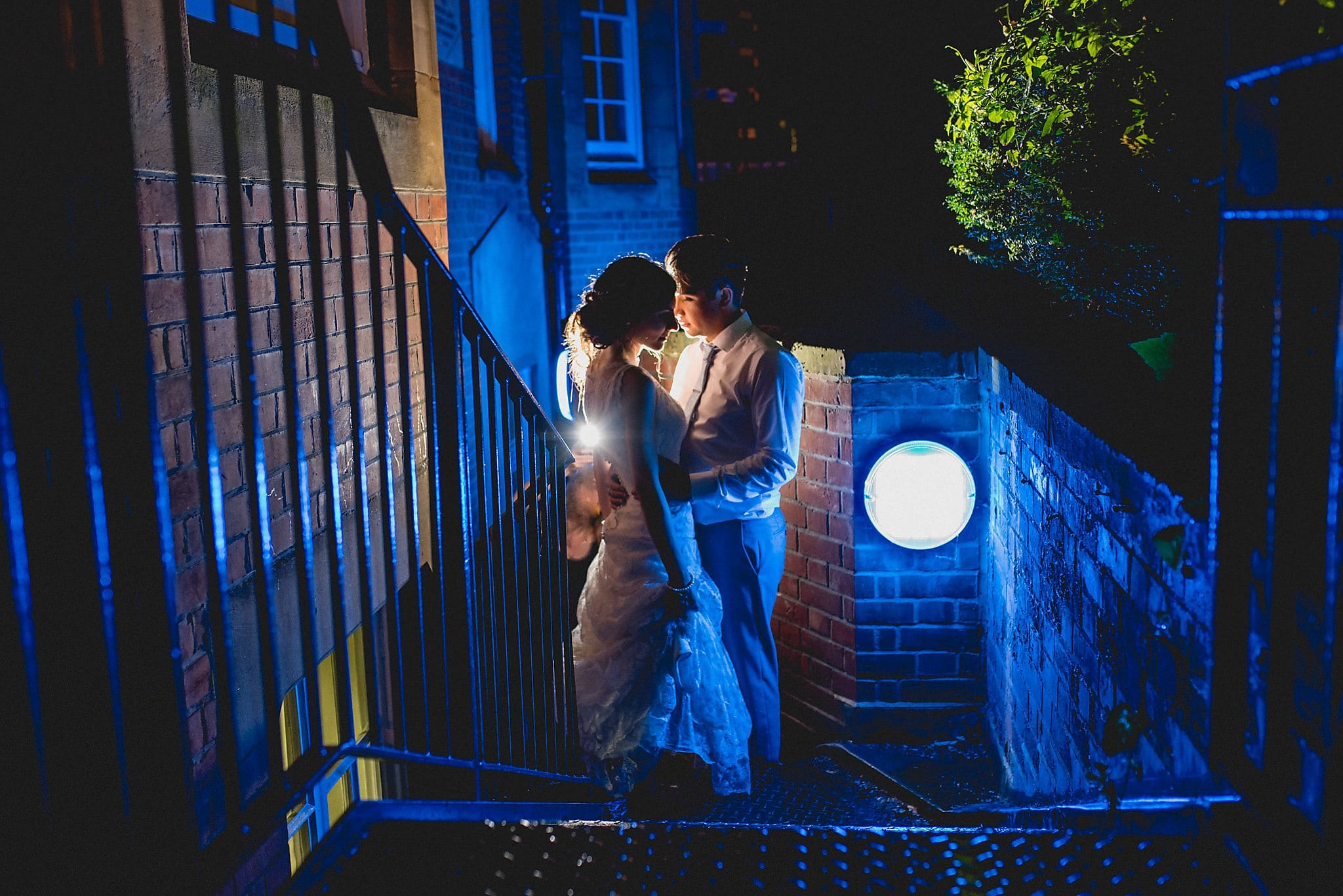 Bride and groom at night, lit by blue light