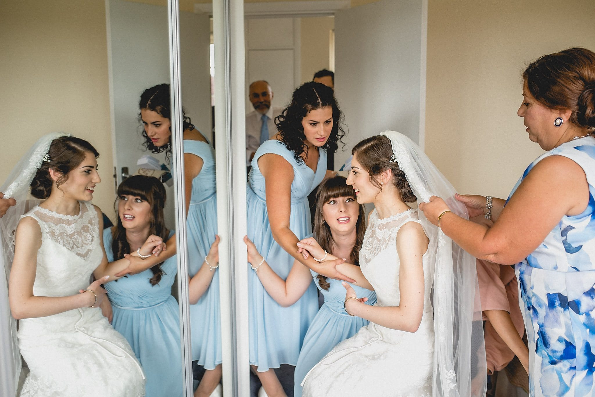 Bridesmaids and Mother of the bride getting the Bride ready for her Modern Greek Wedding