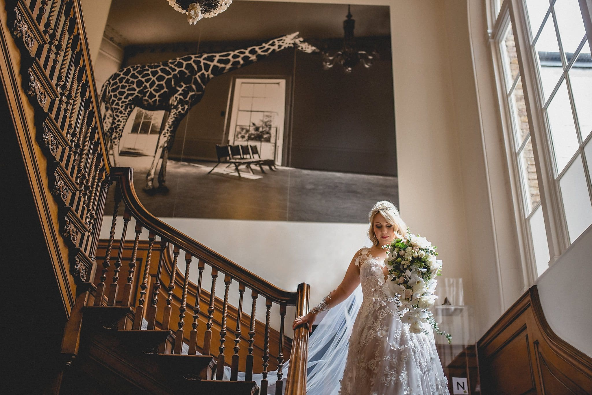 Bride walking down the staircase at her Artistic Wedding at The Grove