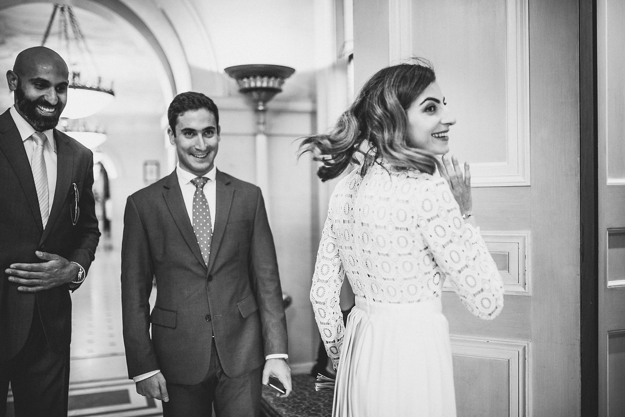 Bride turns to greet guests at her wedding at The Lanesborough