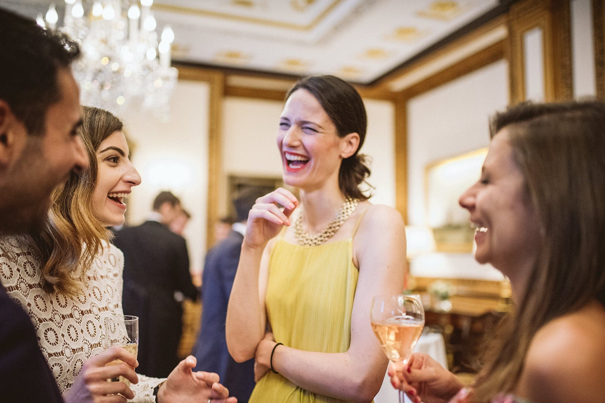 Wedding Guest in yellow dress laughing with the bride and groom