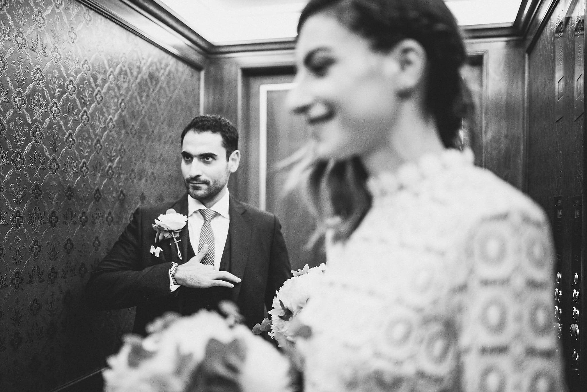 Black and white shot of bride and groom in the lift on the way to their wedding ceremony at The Lanesborough
