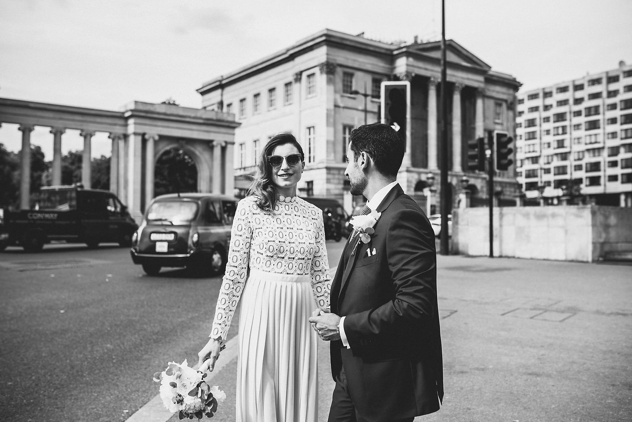 Black and white shot of bride and groom outside The Lanesborough with Hyde Park in the background
