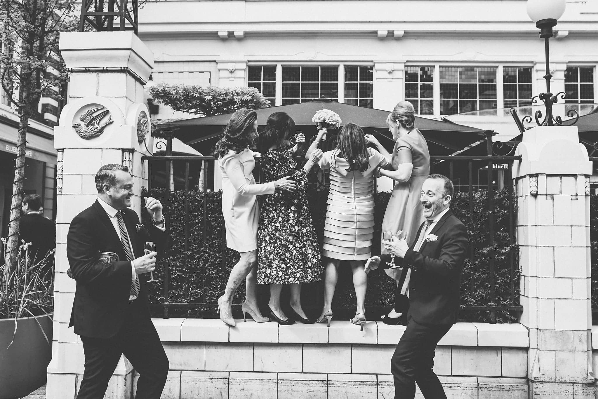 Black and white shot of bride and friends climbing railings outside Chelsea venue