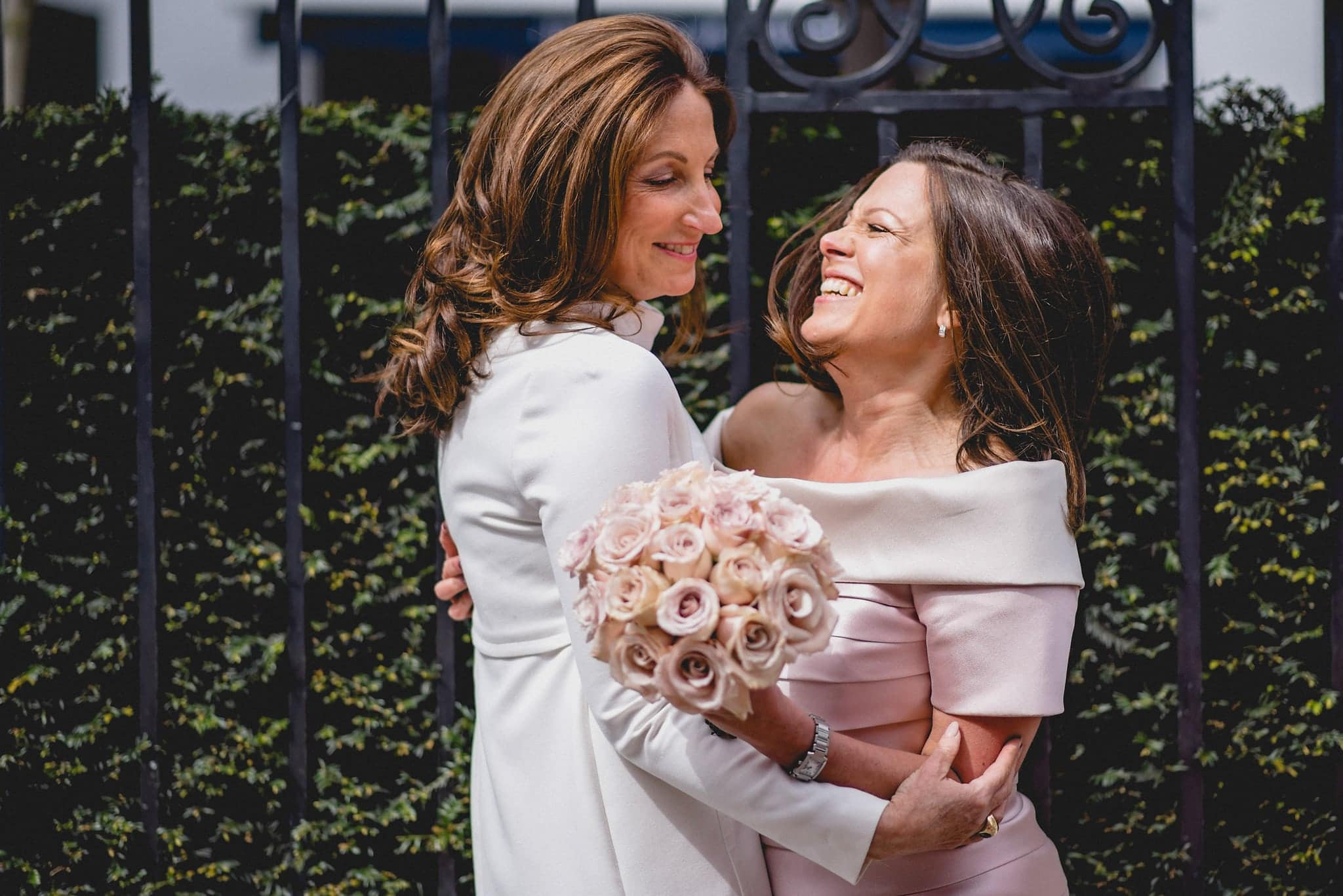 Bride hugs a close friend outside her wedding venue