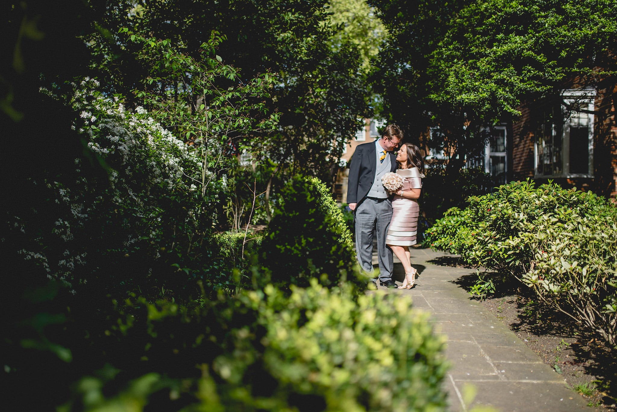 Bride and groom pose together in Chelsea sunshine