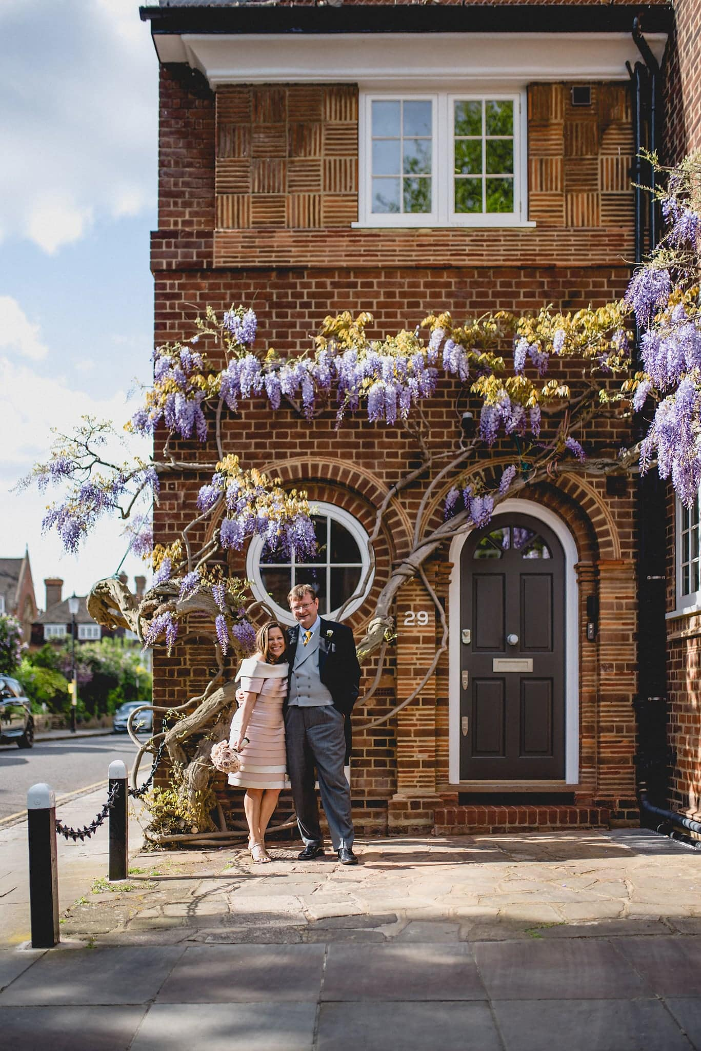 Bride and groom pose outside building draped in wisteria