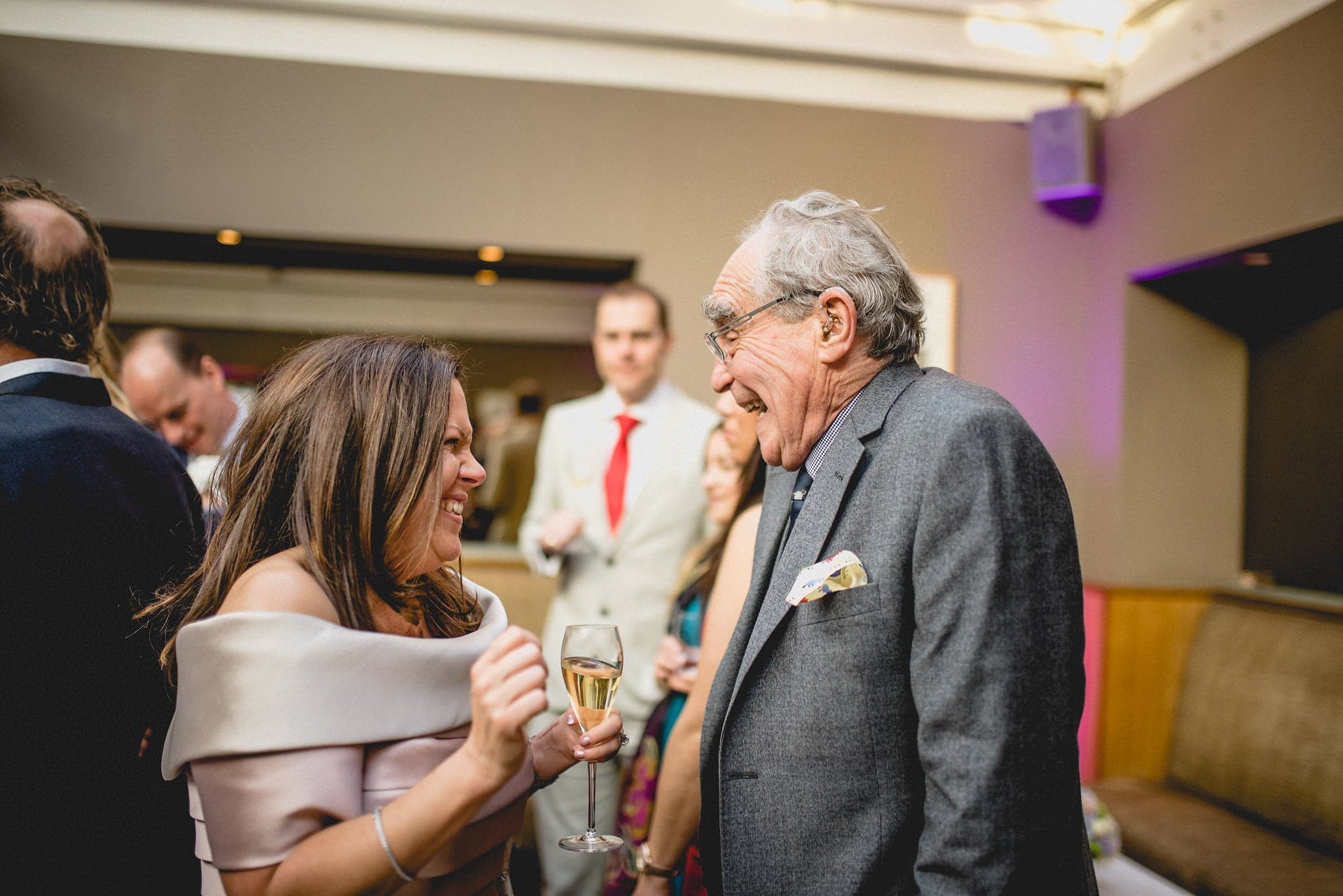 Bride laughing with elderly guest at wedding