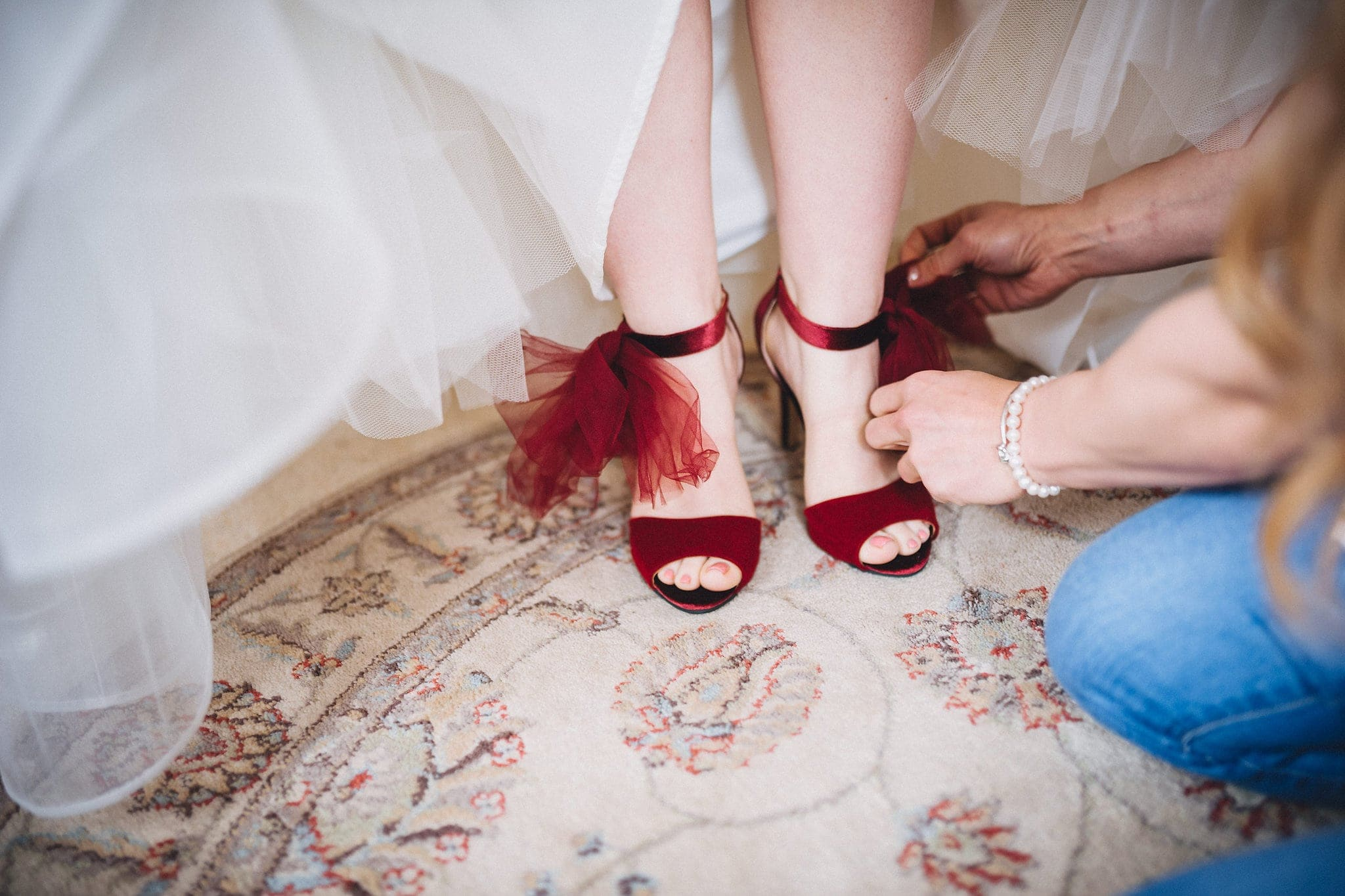 Close up of bride's red velvet wedding shoes